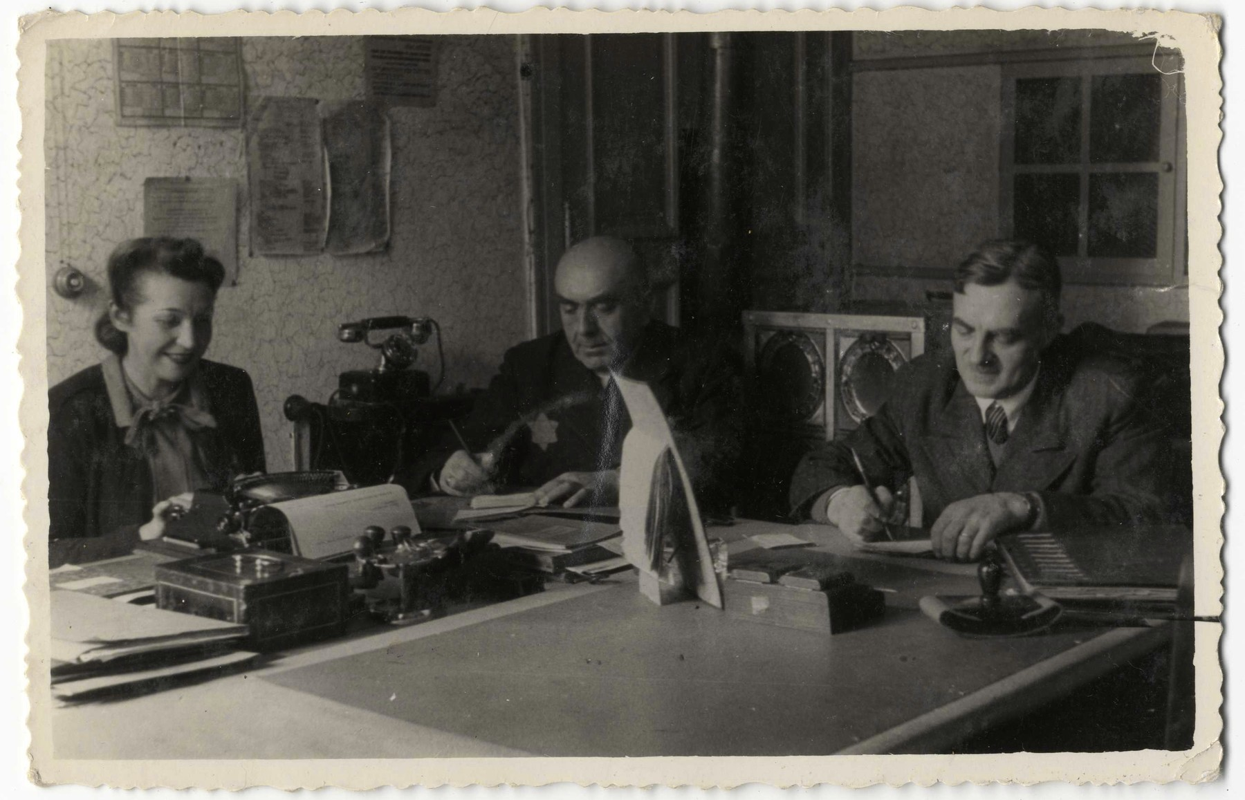 The directors of the Zentral Einkaufstelle, the central purchasing department of the ghetto, work at their desk.  Pictured on the far right is Gustaw Gerson, the director of the Einkaufstelle.  In the center is Lipnowski, the co-director, and Stefa, the secretary is on the left.