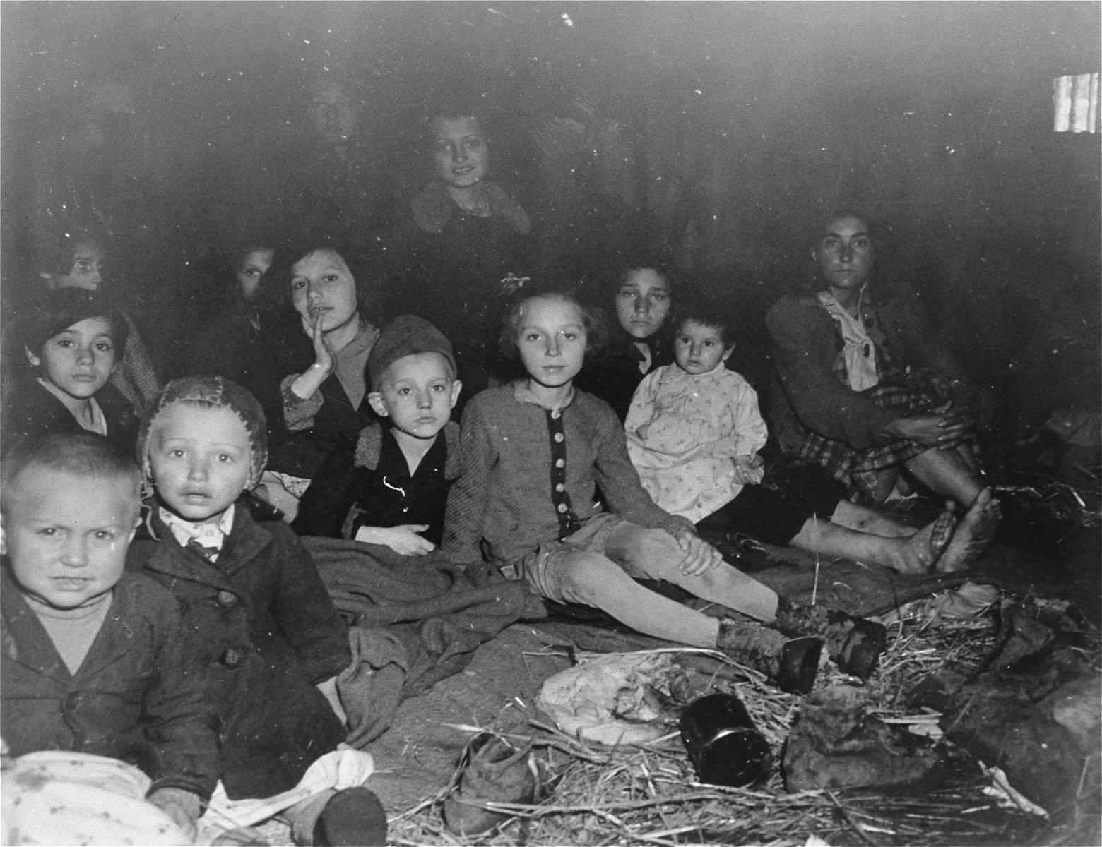Women and children survivors sit on the floor of a barracks in the newly liberated Gunskirchen concentration camp.
