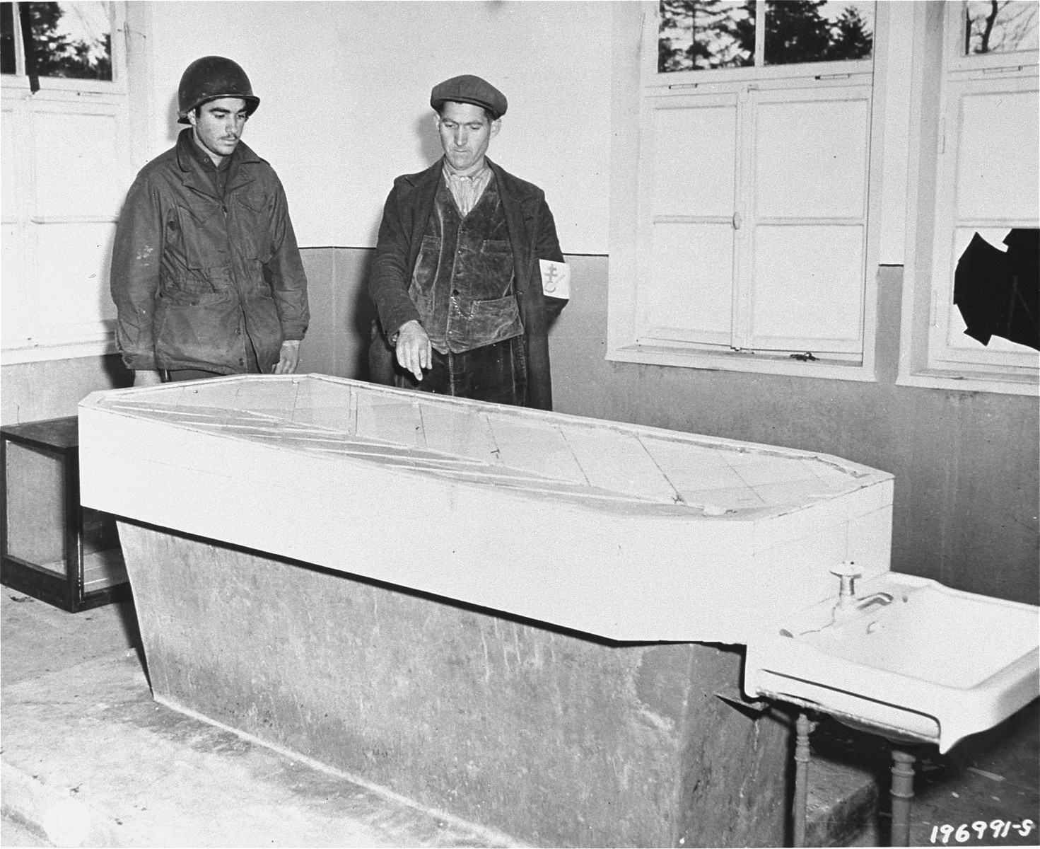 An American soldier and a member of the French resistance examine an autopsy table in the Natzweiler-Struthof concentration camp.