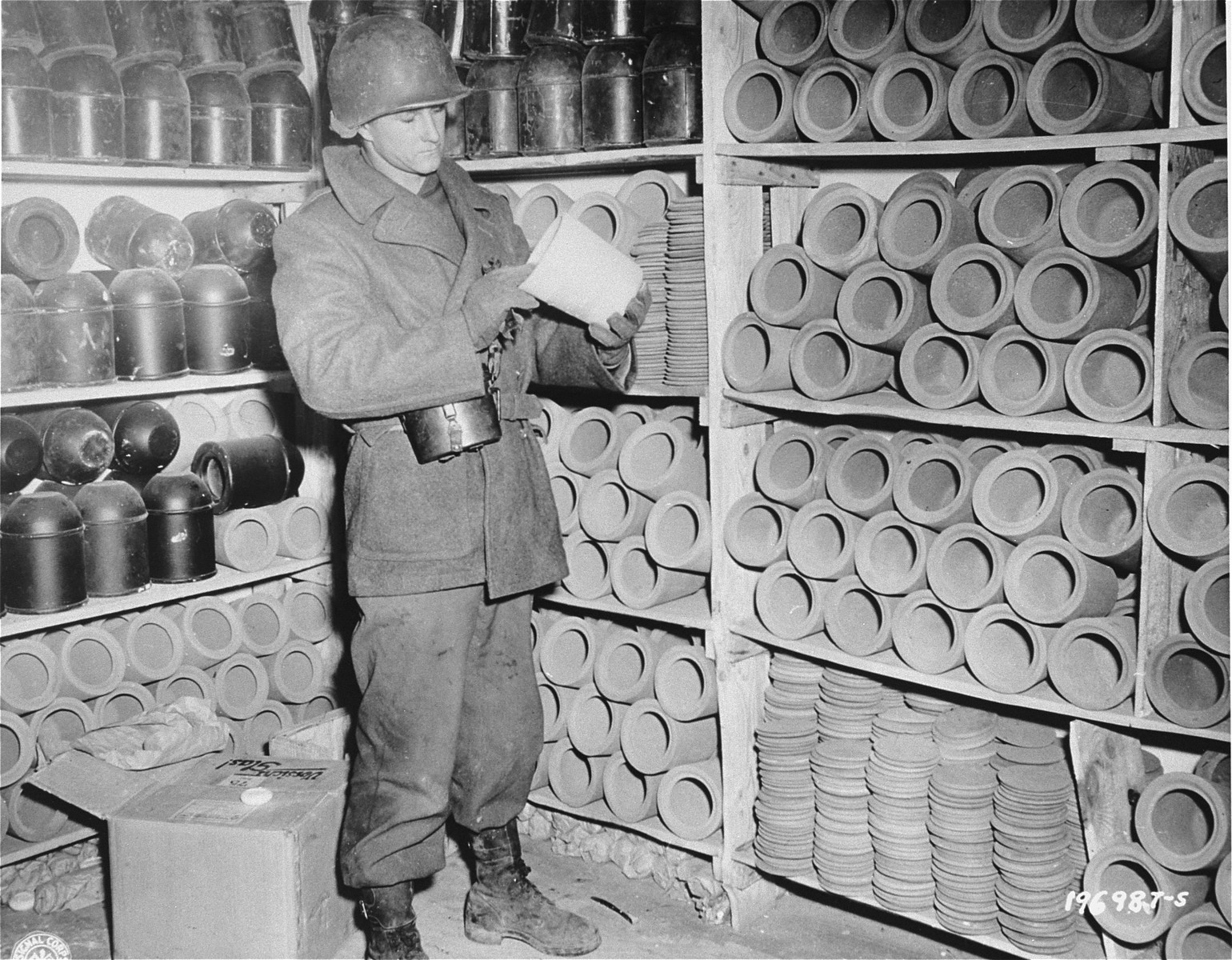 An American soldier in Natzweiler-Struthof examines an urn used to bury the ashes of cremated prisoners.