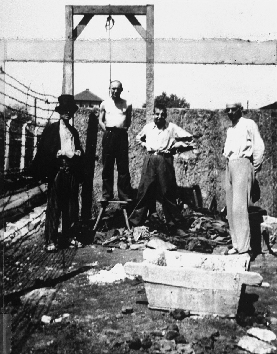 Survivors pose next to a gallows and the shooting wall in the Gusen concentration camp.