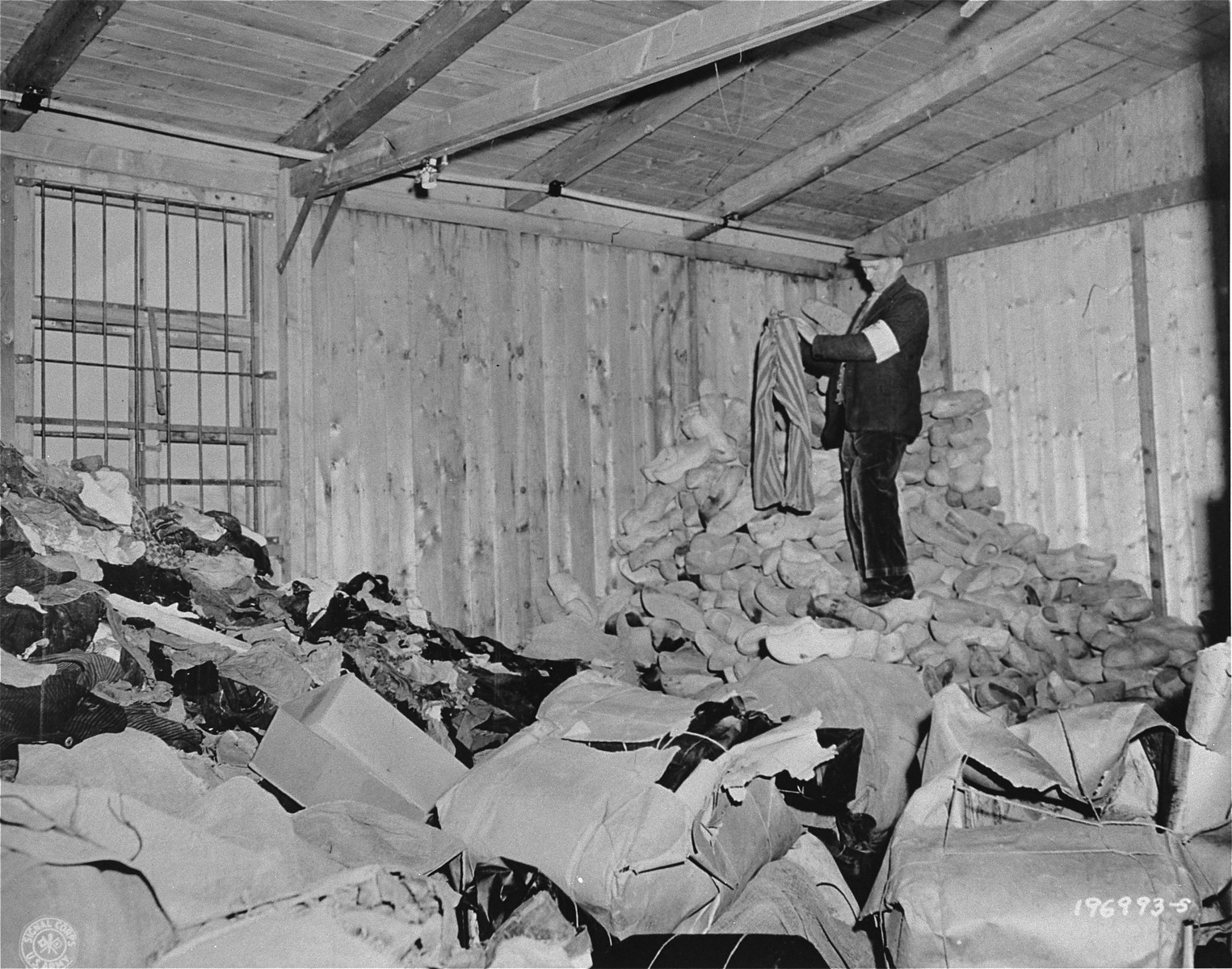 A member of the French resistance sorts through a warehouse filled with discarded prisoners' clothing in the Natzweiler-Struthof concentration camp.