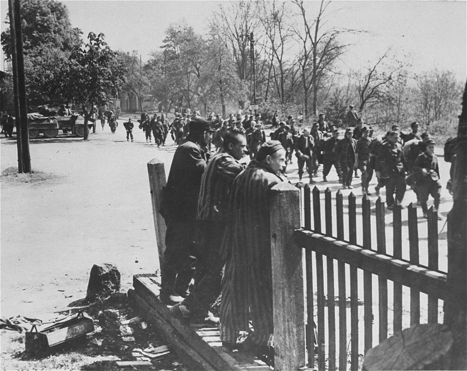 Three survivors from Gusen watch a passing column of German troops who have surrendered to the U.S. Army.
