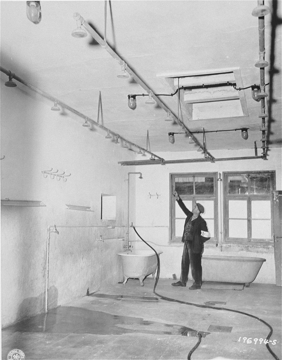 A member of the French resistance points to pipes in the shower room of Natzweiler-Struthof from which prisoners were hung and beaten by SS guards.