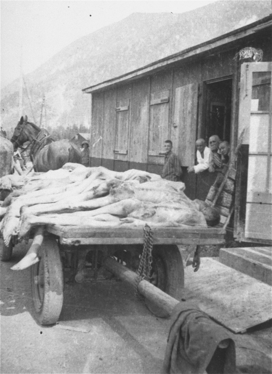 Survivors look on as the bodies of former prisoners are removed from a barracks in the newly liberated Ebensee concentration camp.