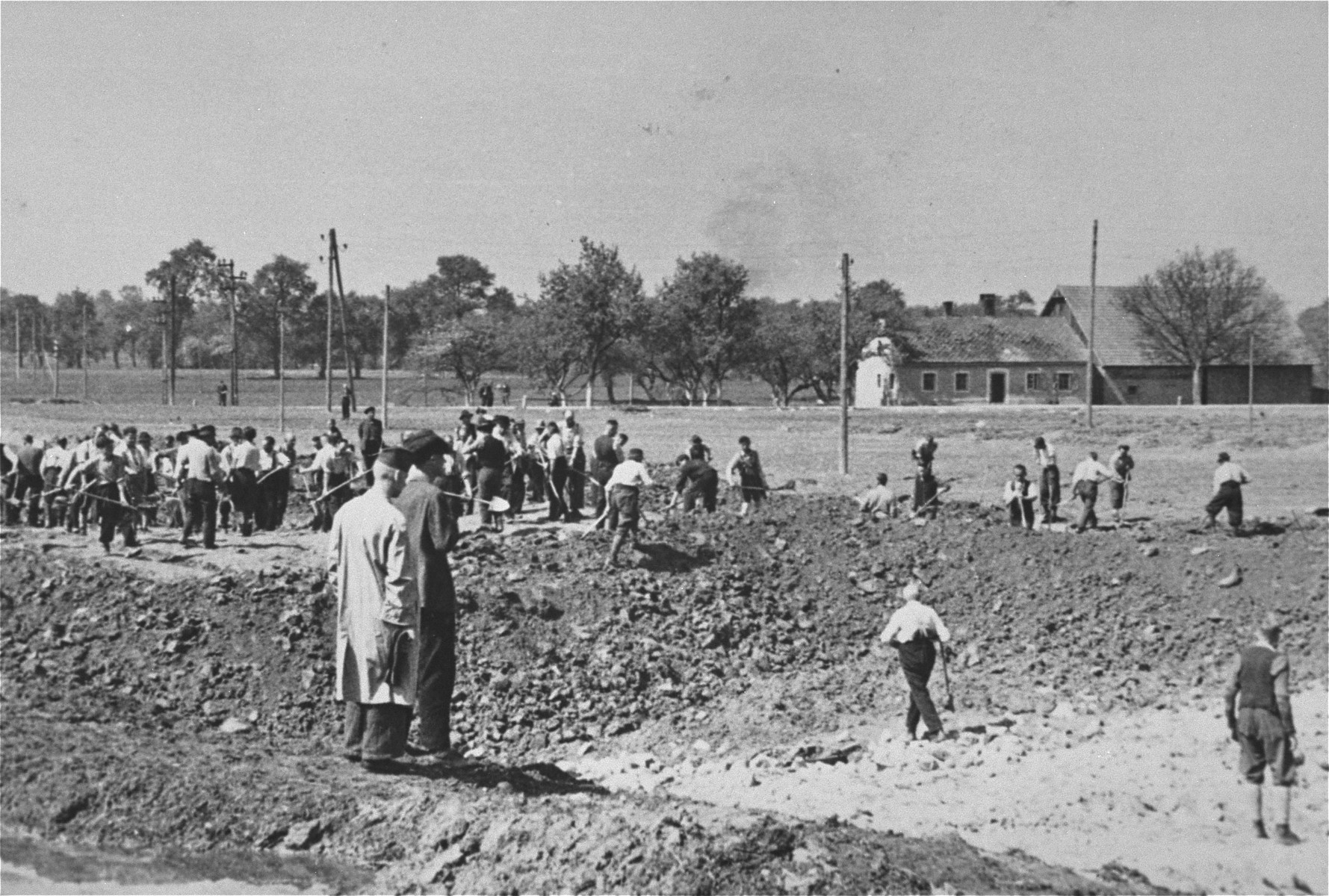 Austrian civilians prepare mass graves to bury former deceased prisoners in the Gusen concentration camp.
