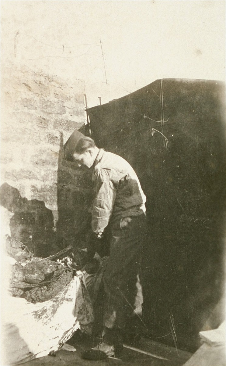 An American soldier prepares a corpse of a prisoner for burisal  in Ebensee.