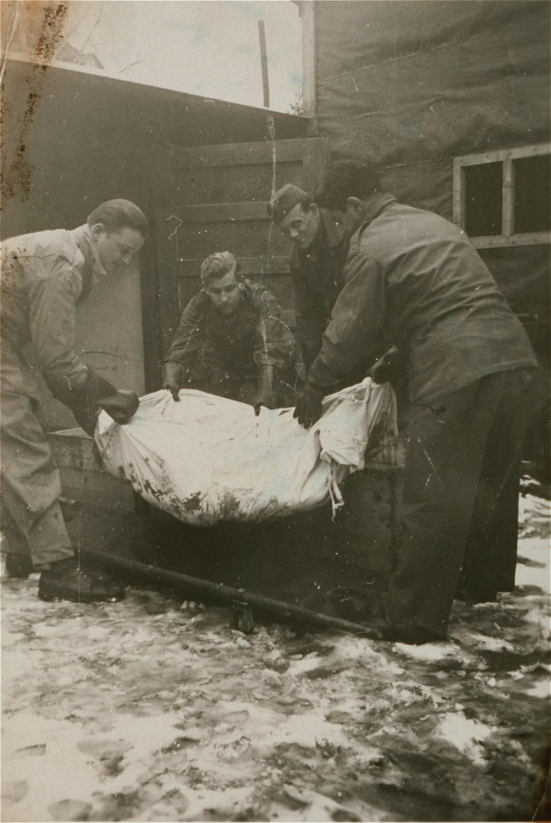 American troops loadi a corpse into a coffin at Ebensee.