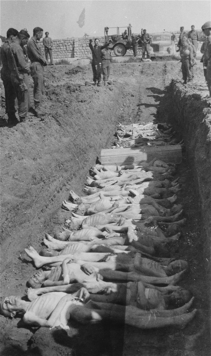 An American Army chaplain recites prayers at an open mass grave in the Gusen concentration camp.