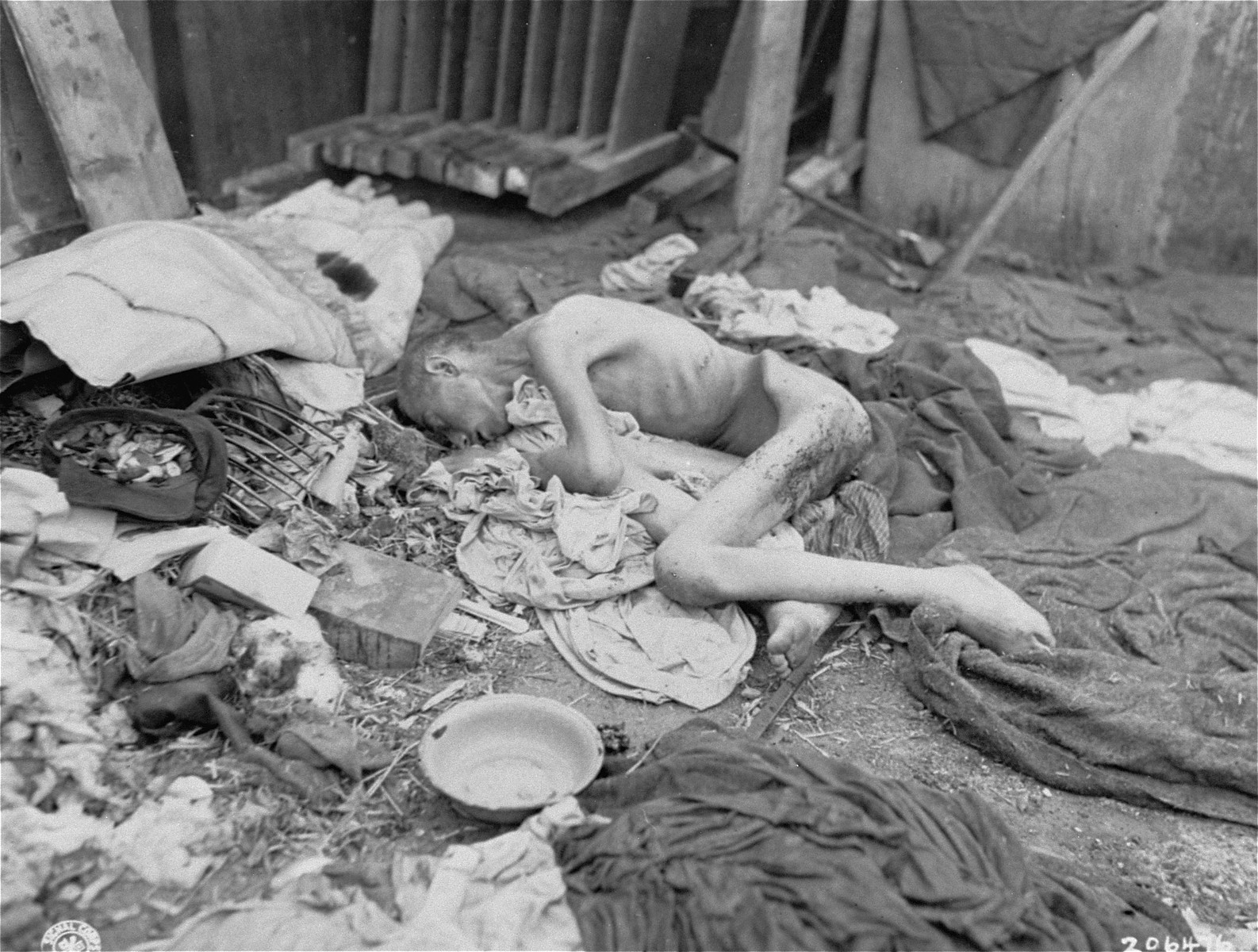 An emaciated survivor lies on the ground among blankets and bowls in the newly liberated Gusen concentration camp.