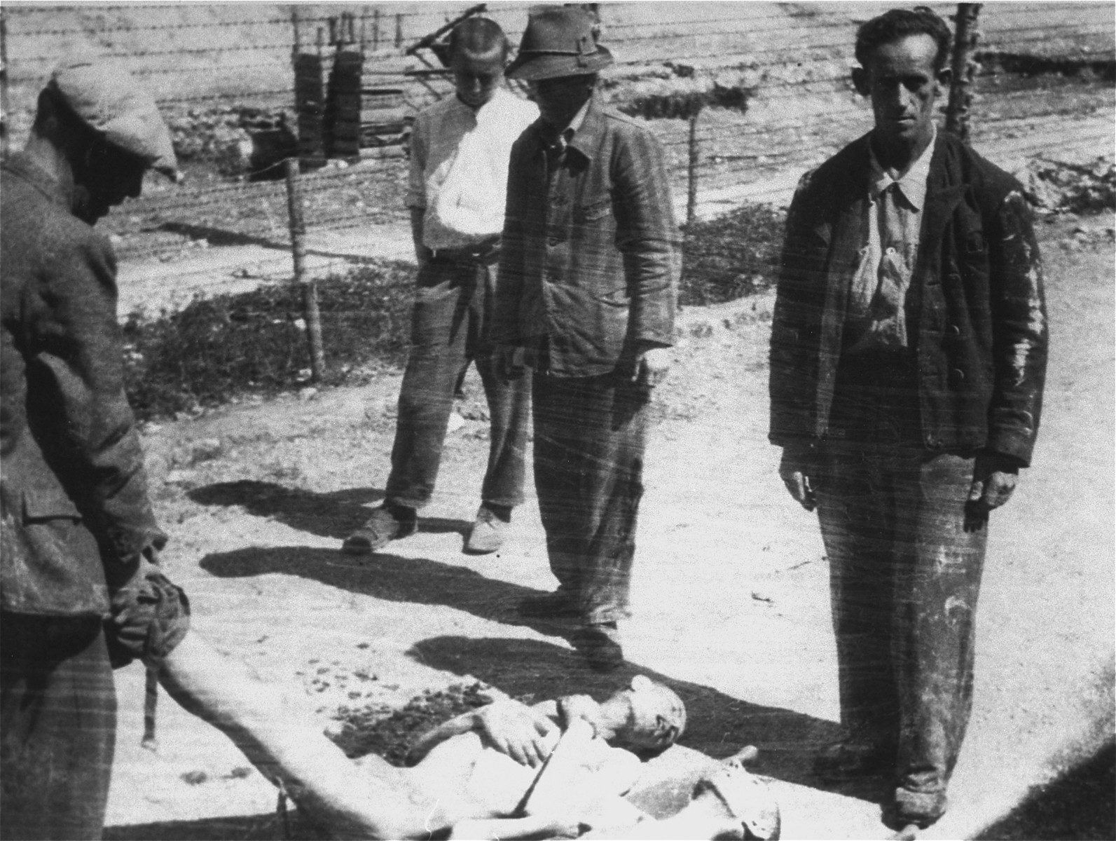 Survivors in Ebensee collect the bodies of fellow prisoners for burial.
