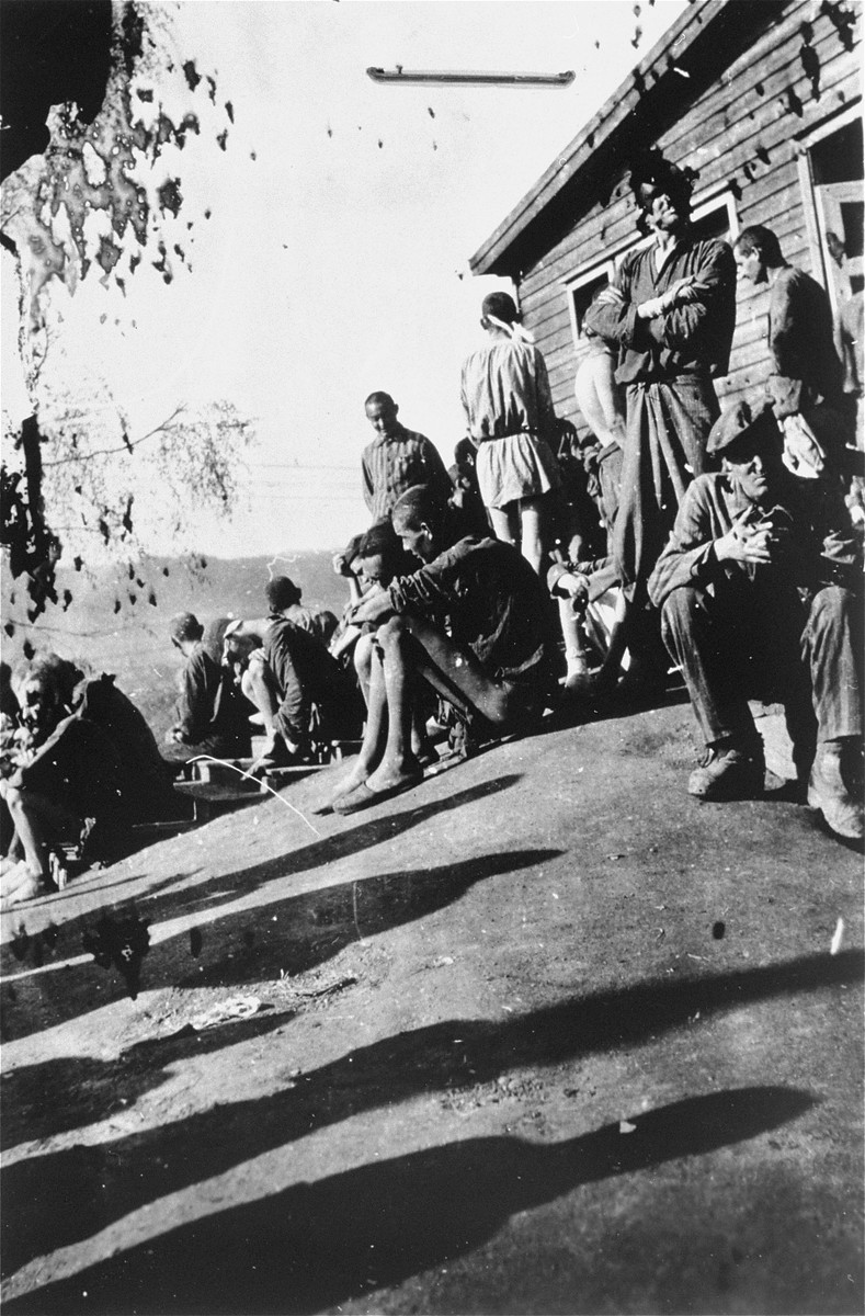 Survivors [probably of Gusen] stand outside of a barracks.