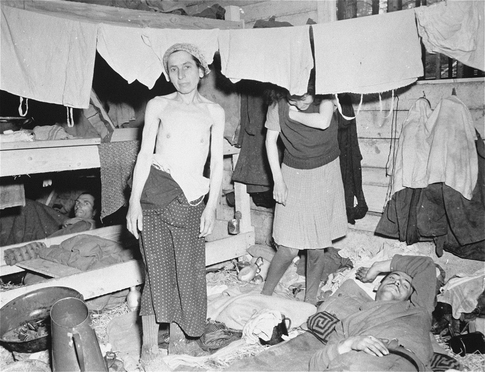 Emaciated female survivors stand beneath hanging laundry in the newly liberated Gunskirchen concentration camp.