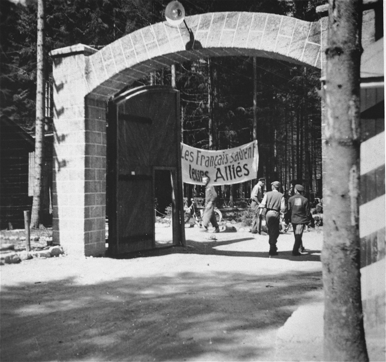 """View of the main gate at the Ebensee concentration camp.  The sign just beyond it reads: """"The French prisoners salute the Allies."""""""