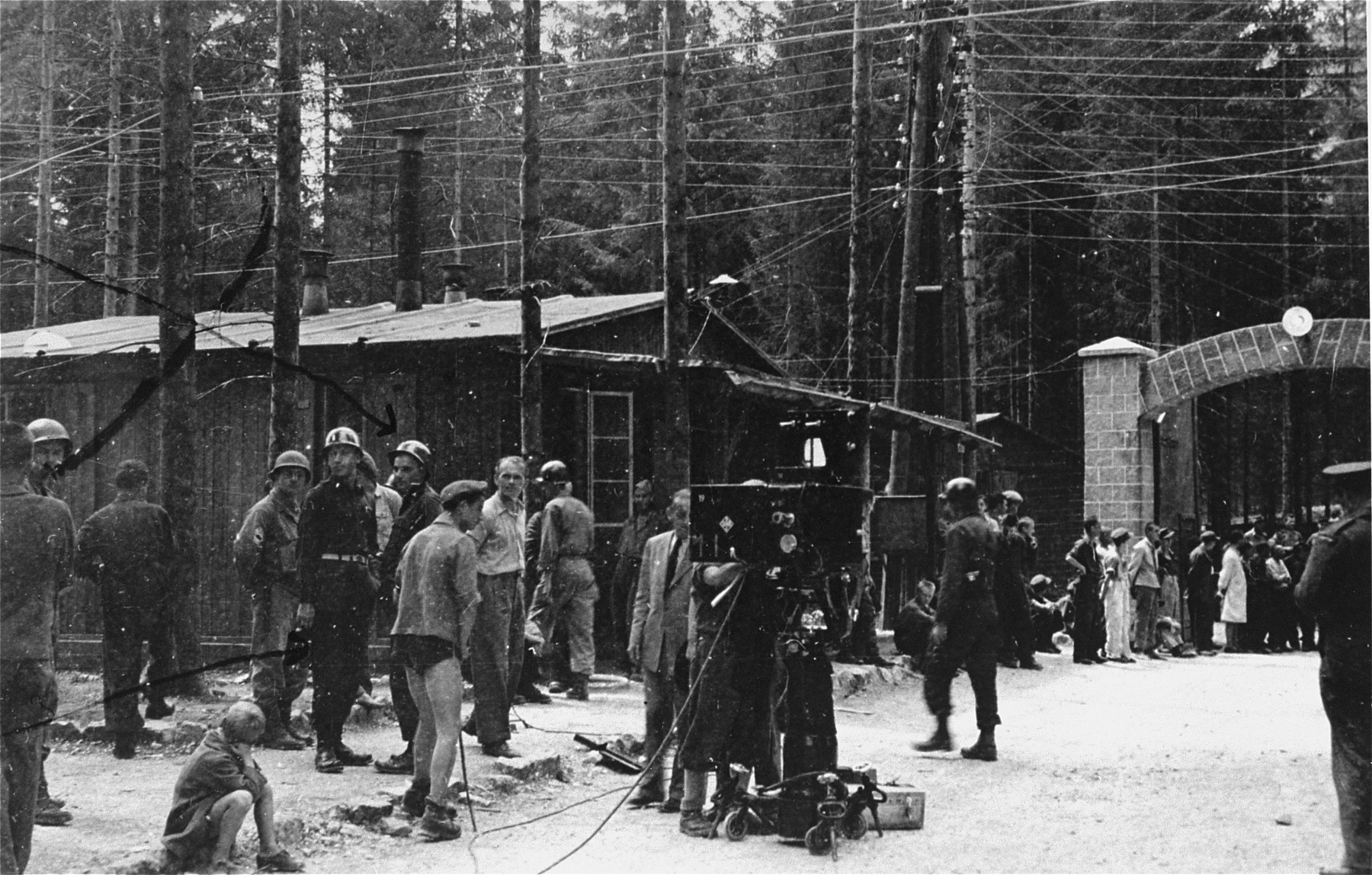 Survivors and American soldiers stand at the entrance to the Ebensee concentration camp and watch as a film crew sets up its equipment.