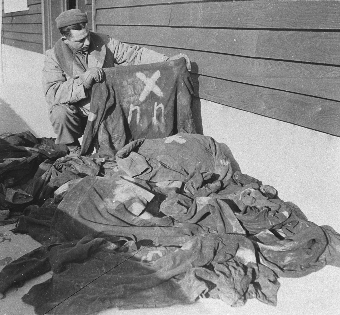 """An American soldier examines markings on prisoners' clothing in Natzweiler-Struthof.    The """"N N"""" on the back of the shirt he is holding stands for """"Nacht und Nebel"""" (Night and Fog).  NN prisoners were interned for acts of resistance and were executed under orders of a Hitler Decree."""