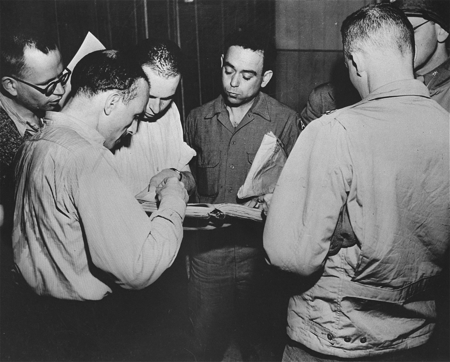 Corporal Jack R. Nowitz (center), a lawyer on the staff of the Judge Advocate General, 3rd U.S. Army, checks books listing exterminations at Gusen.