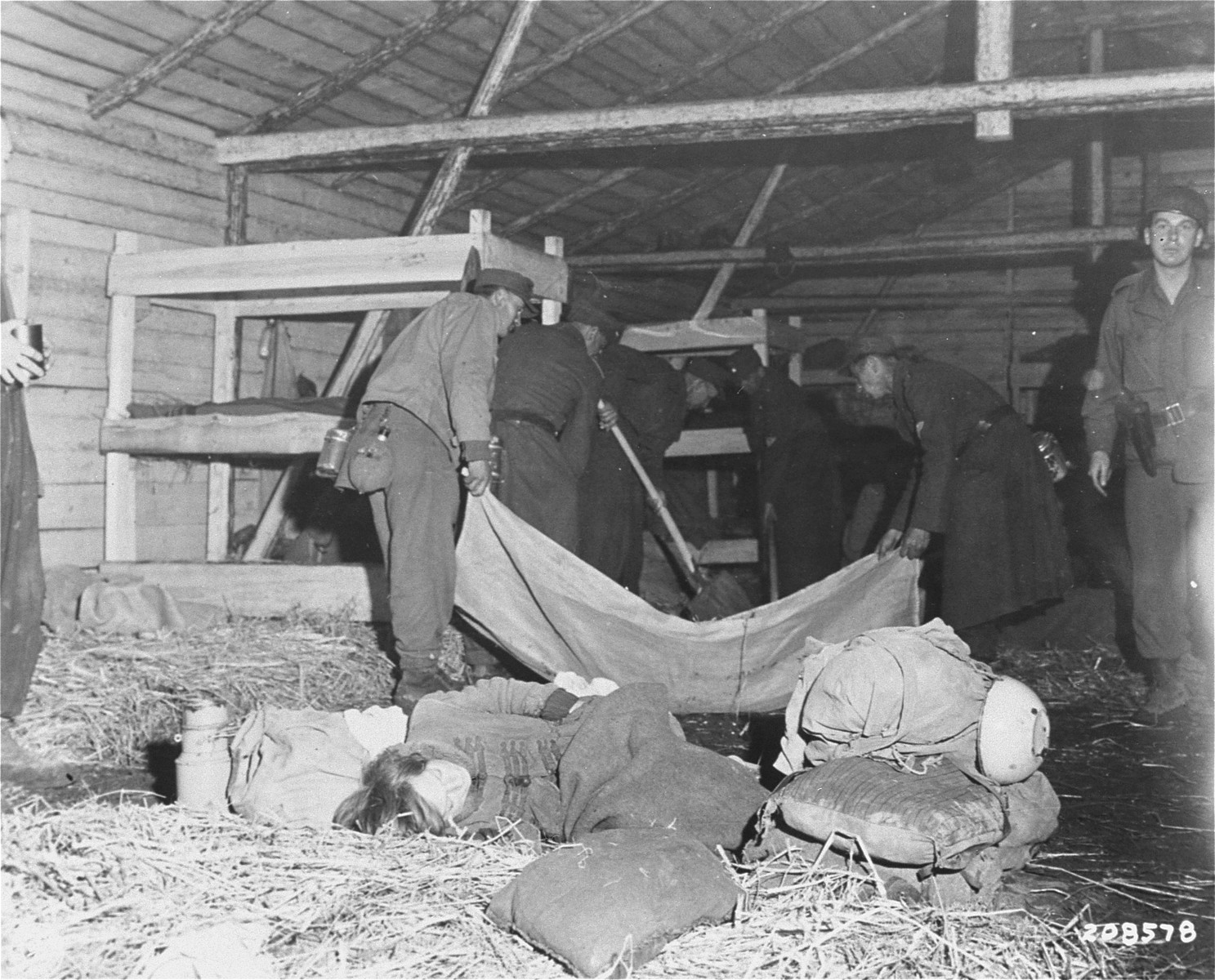 Medical corpsmen of the U.S. 71st Infantry Division, 3rd U.S. Army look on as captured German soldiers remove bodies from inside a barracks in Gunskirchen.  In the foreground, a Jewish girl lies huddled in the straw on the floor of the barracks.