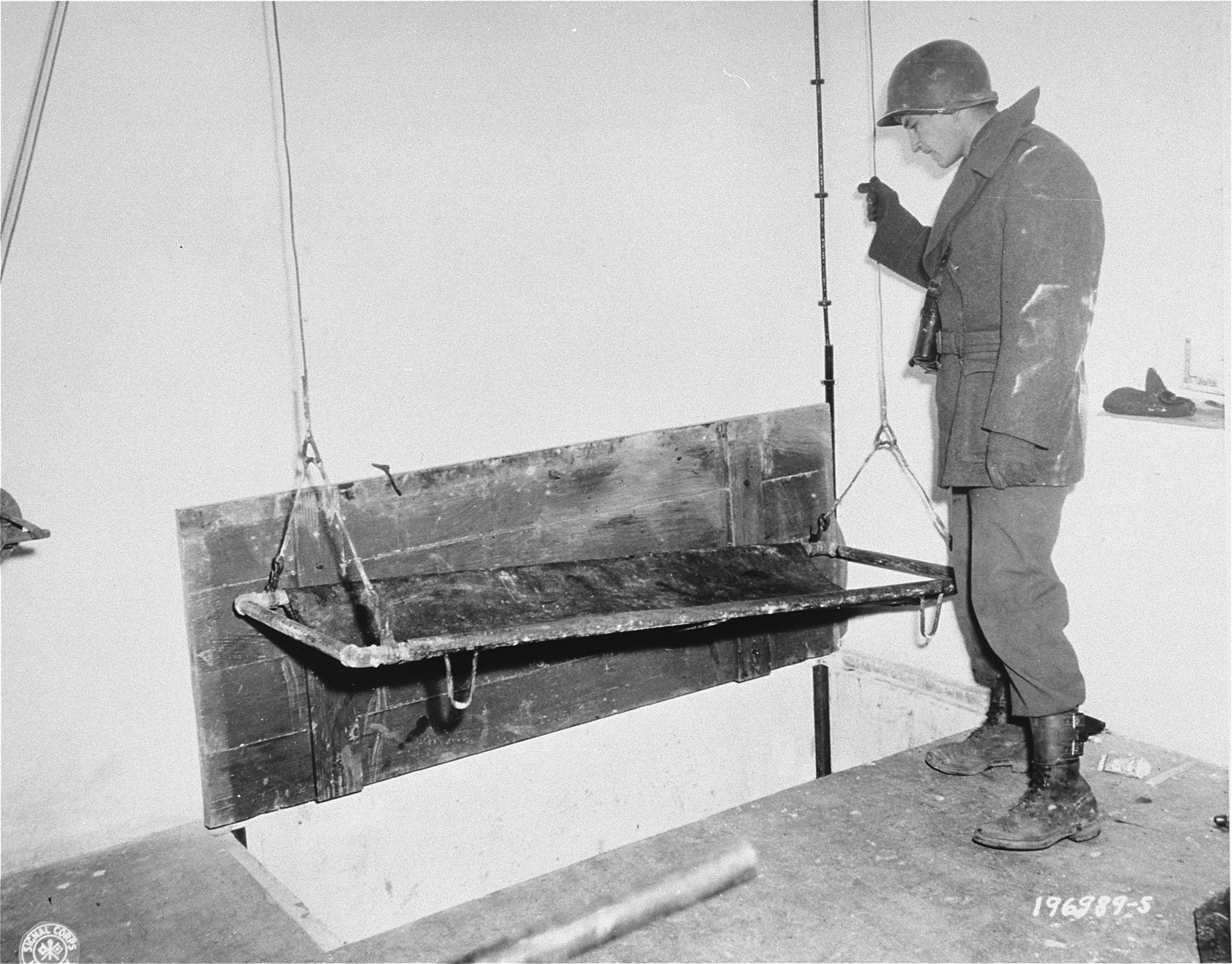 An American soldier tests the crematorium elevator while on an inspection of the Natzweiler-Struthof concentration camp.