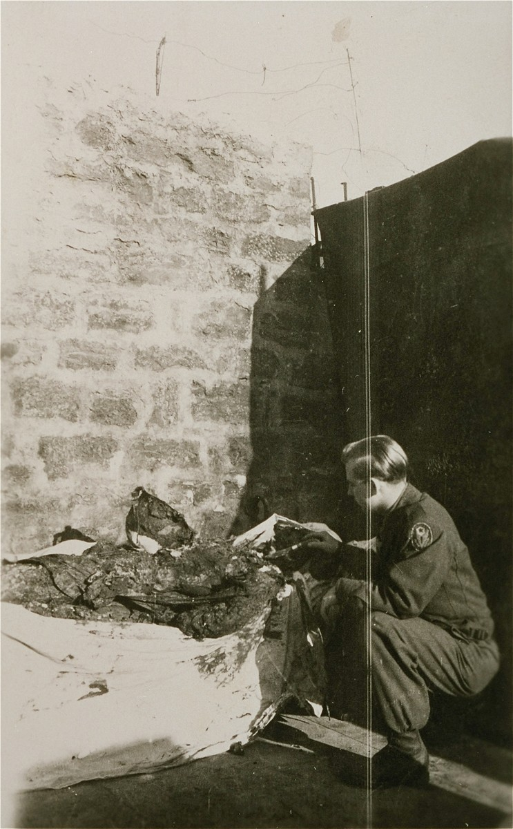 An American soldier in Ebensee examines the exhumed remains of a prisoner.