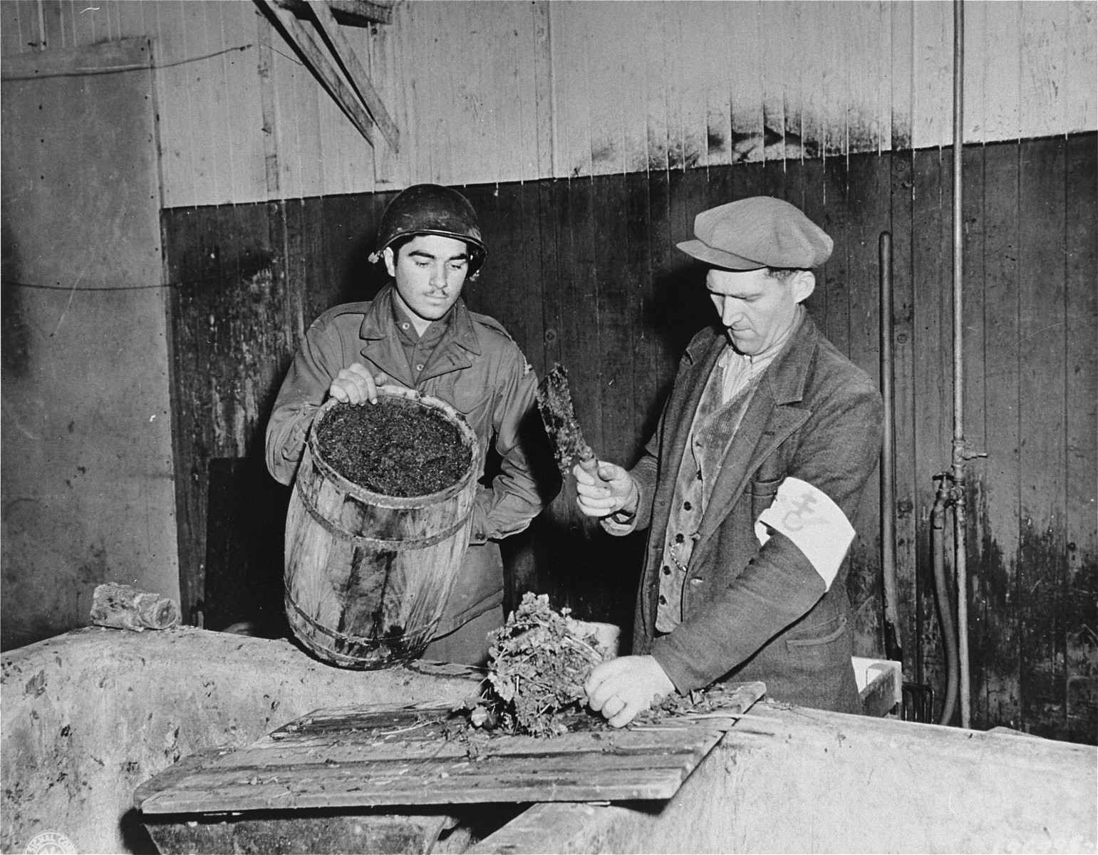A member of the French resistance demonstrates for an American soldier the method of preparing chopped potatoes, the staple of the inmates' diet.