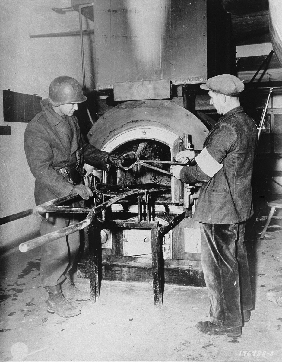 An American soldier and member of the French resistance inspect the crematorium in Natzweiler-Struthof.  They are holding a pair of tongs that were used to handle the bodies.