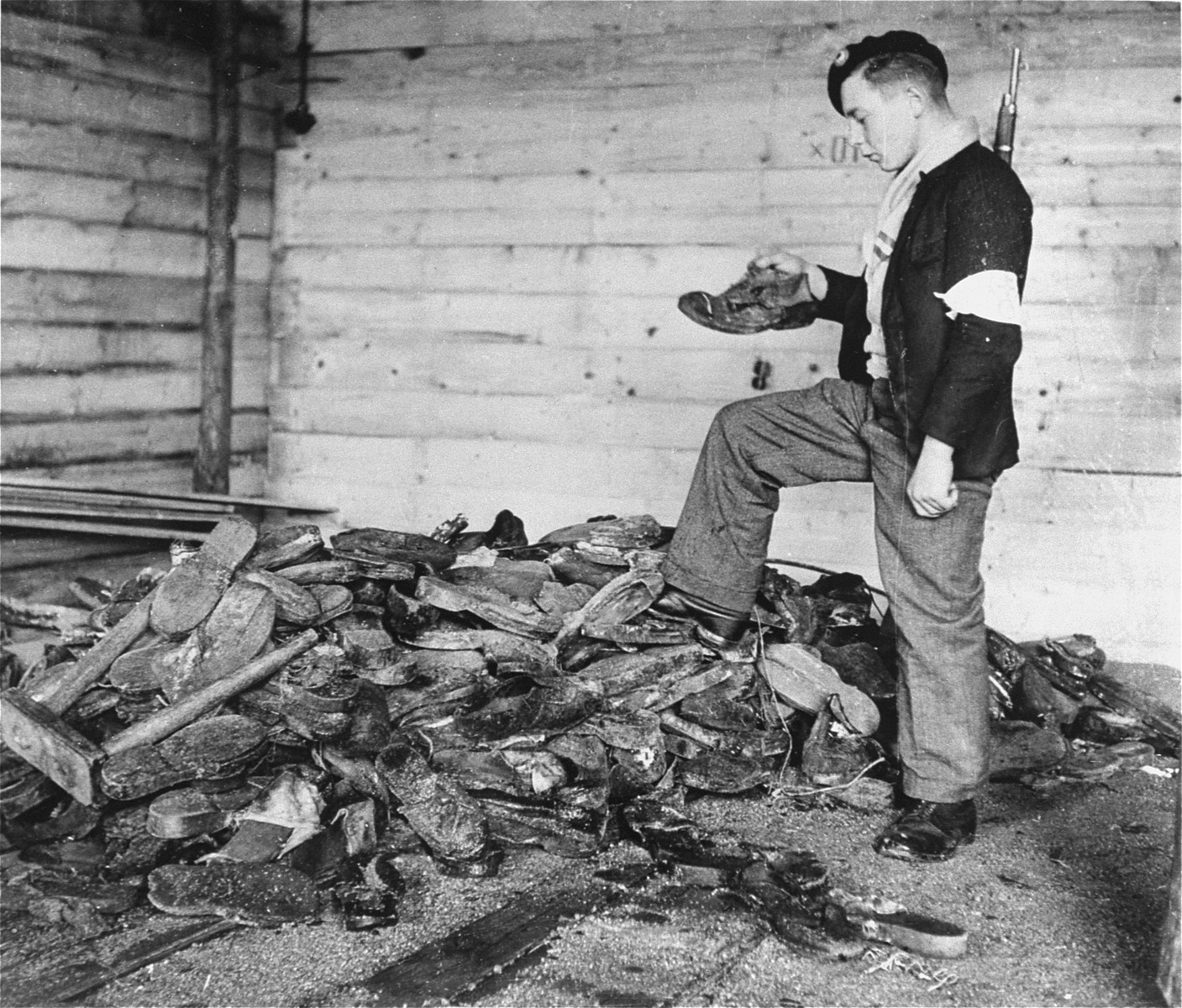 A young member of the French resistance examines boots, shoes, and wooden clogs piled near a furnace in the crematorium of the Natzweiler-Struthof concentration camp.