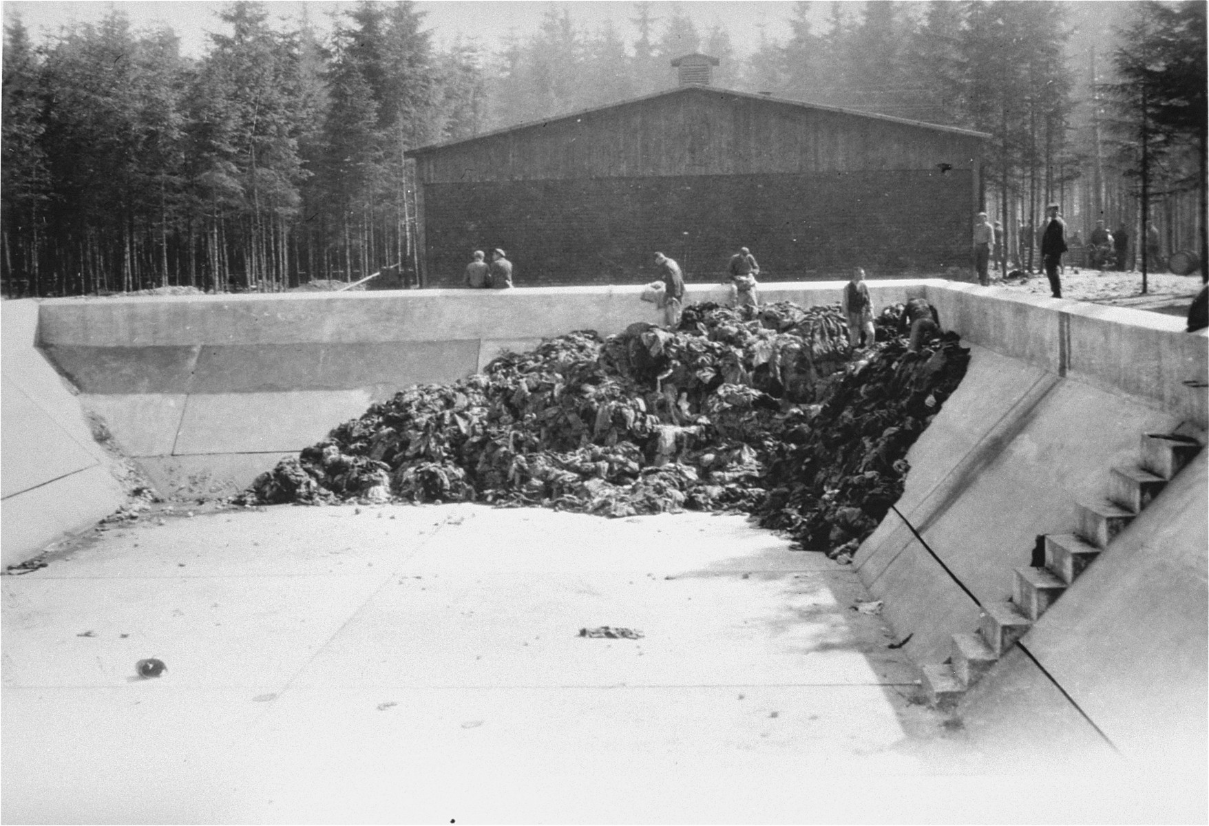 View of the pool in the Ebensee concentration camp where clothing that has been stripped off the dead is being collected.