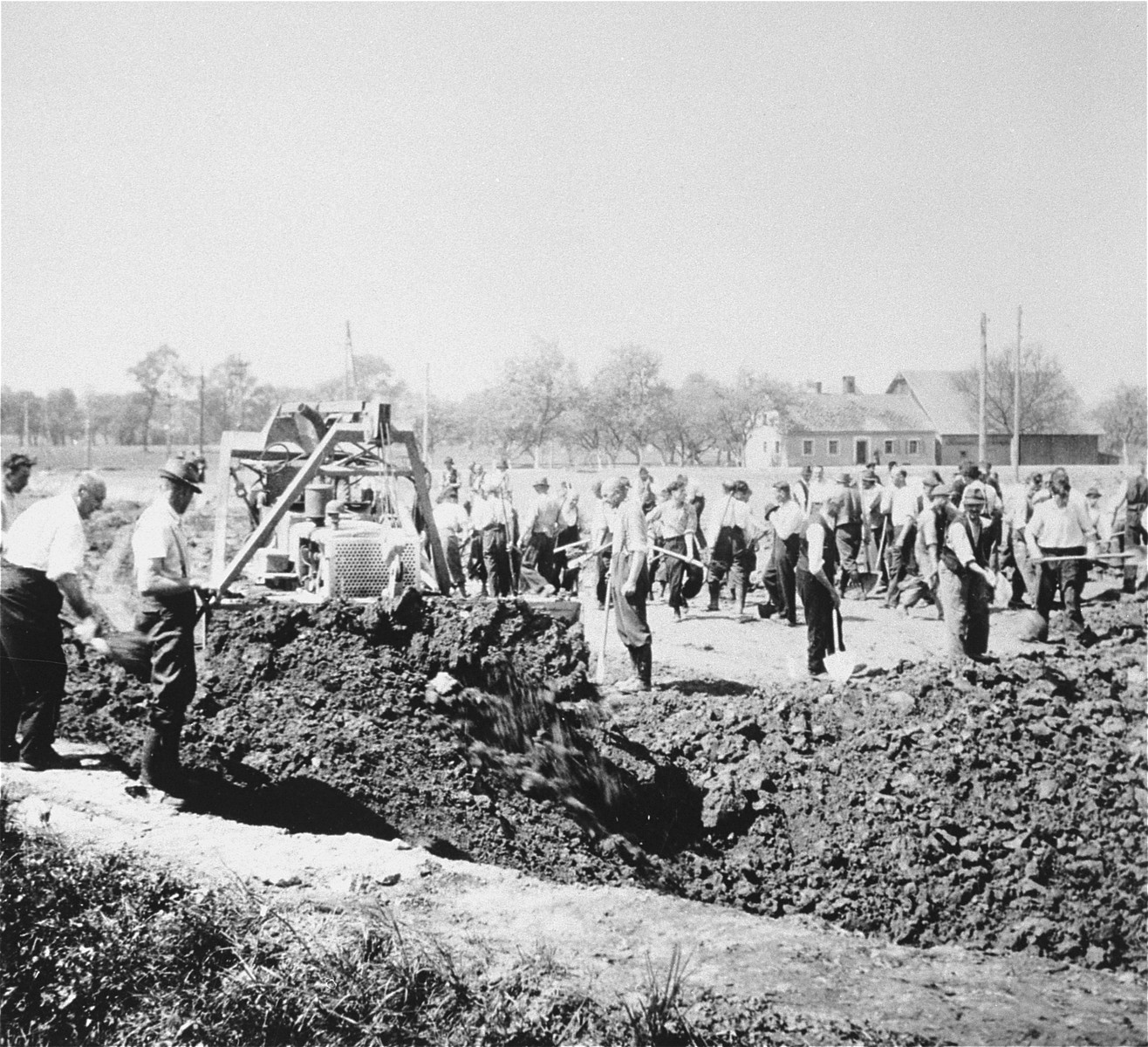 Austrian civilians prepare a mass grave to bury former inmates in the Gusen concentration camp, while a bulldozer levels the ground over an already filled grave.