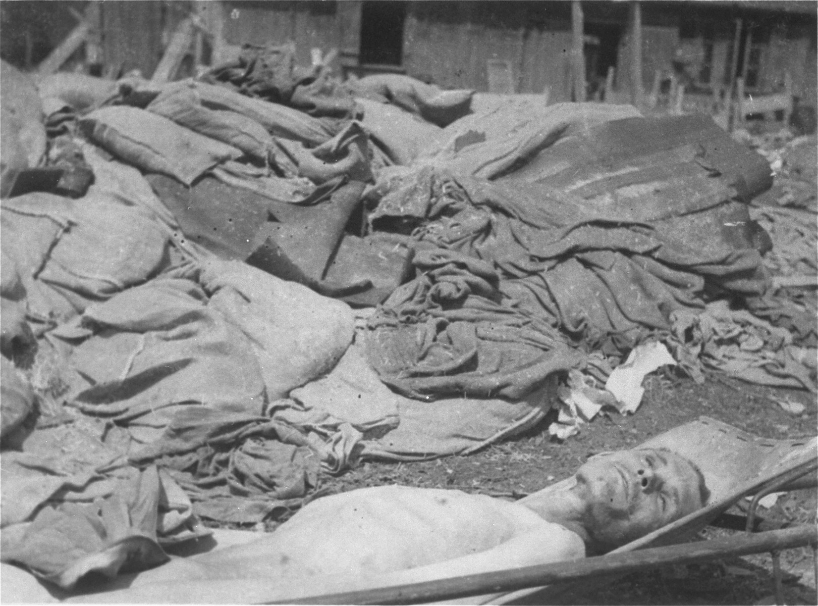 The body of a former prisoner lies outside on a stretcher next to a pile of clothing in the newly liberated Ebensee concentration camp.