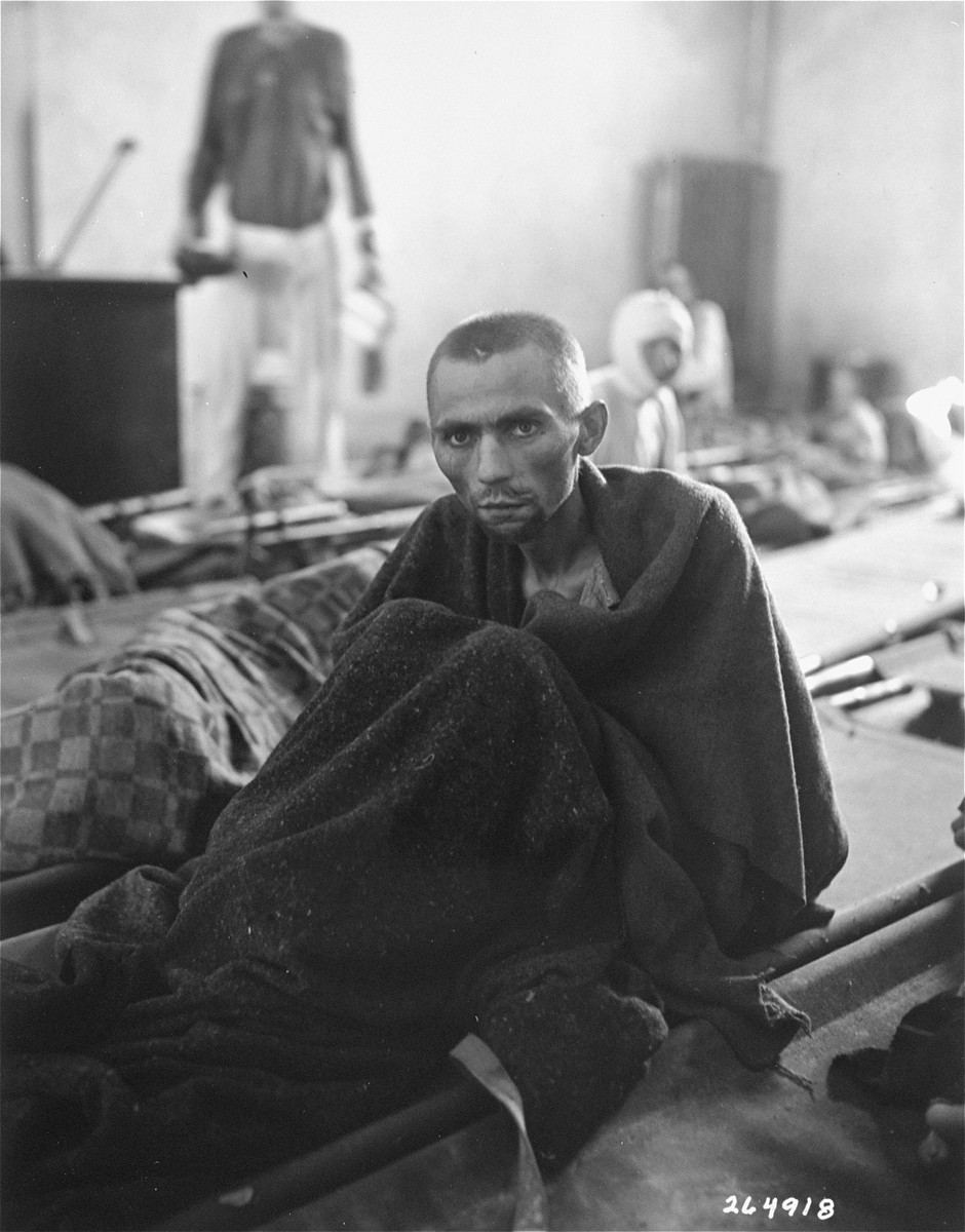An emaciated survivor wrapped in a blanket sits up on a stretcher in the newly liberted Gusen concentration camp.