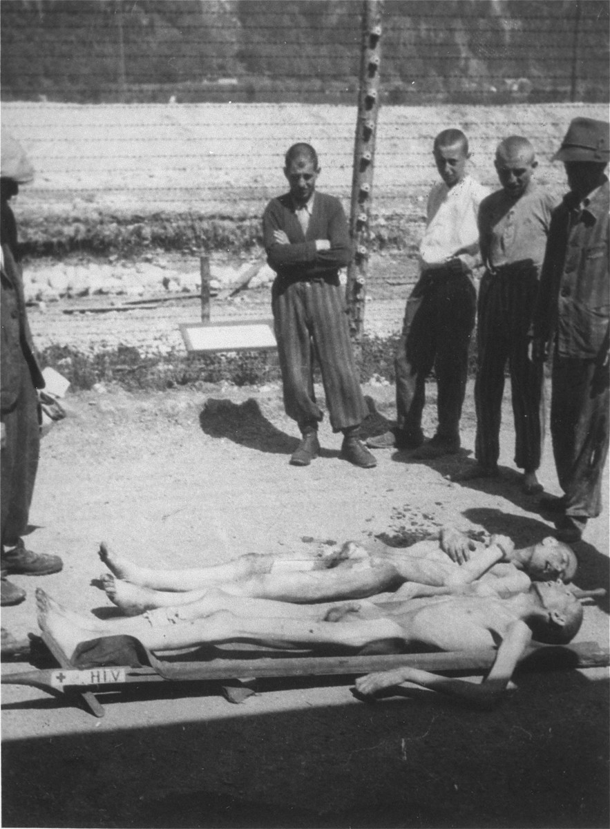 Survivors in Ebensee collect the bodies of dead fellow prisoners for burial.