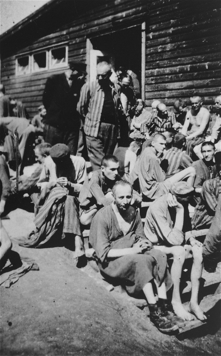 Survivors in [probably of Gusen] gather outside of a barrack.