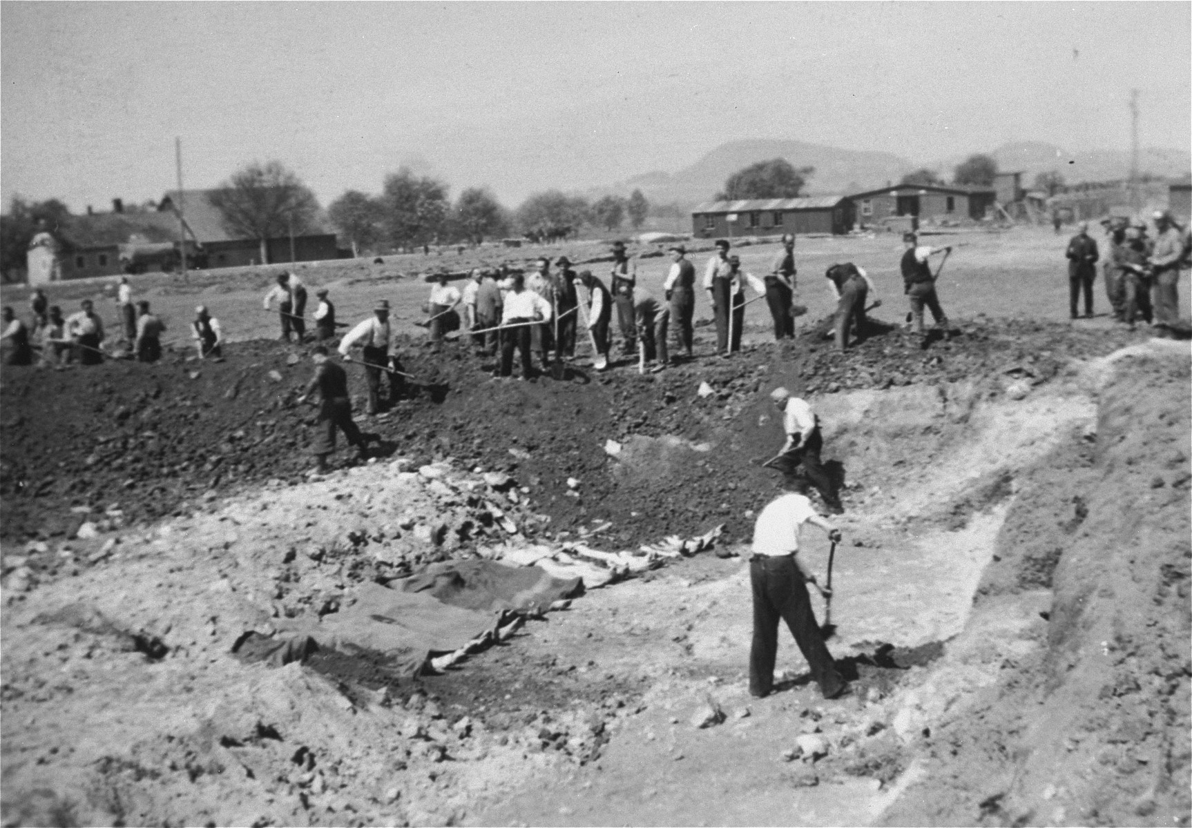 Austrian civilians prepare mass graves to bury the bodies of former concentration camp inmates at Gusen.