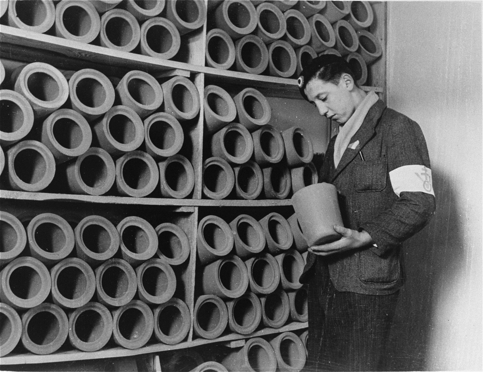 A member of the French resistance examines urns used to bury prisoners' cremated remains in Natzweiler-Struthof.