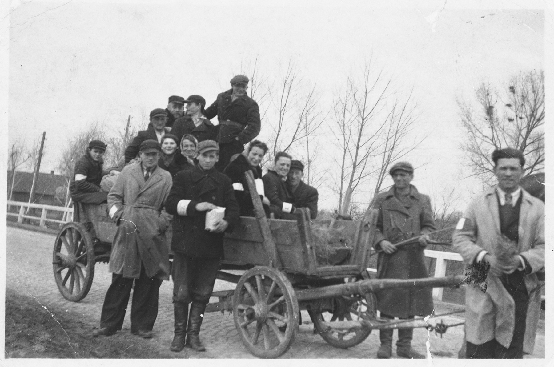 A group of Jewish friends wearing armbands poses on and around a hay wagon near Radom shortly after the German invasion of Poland.