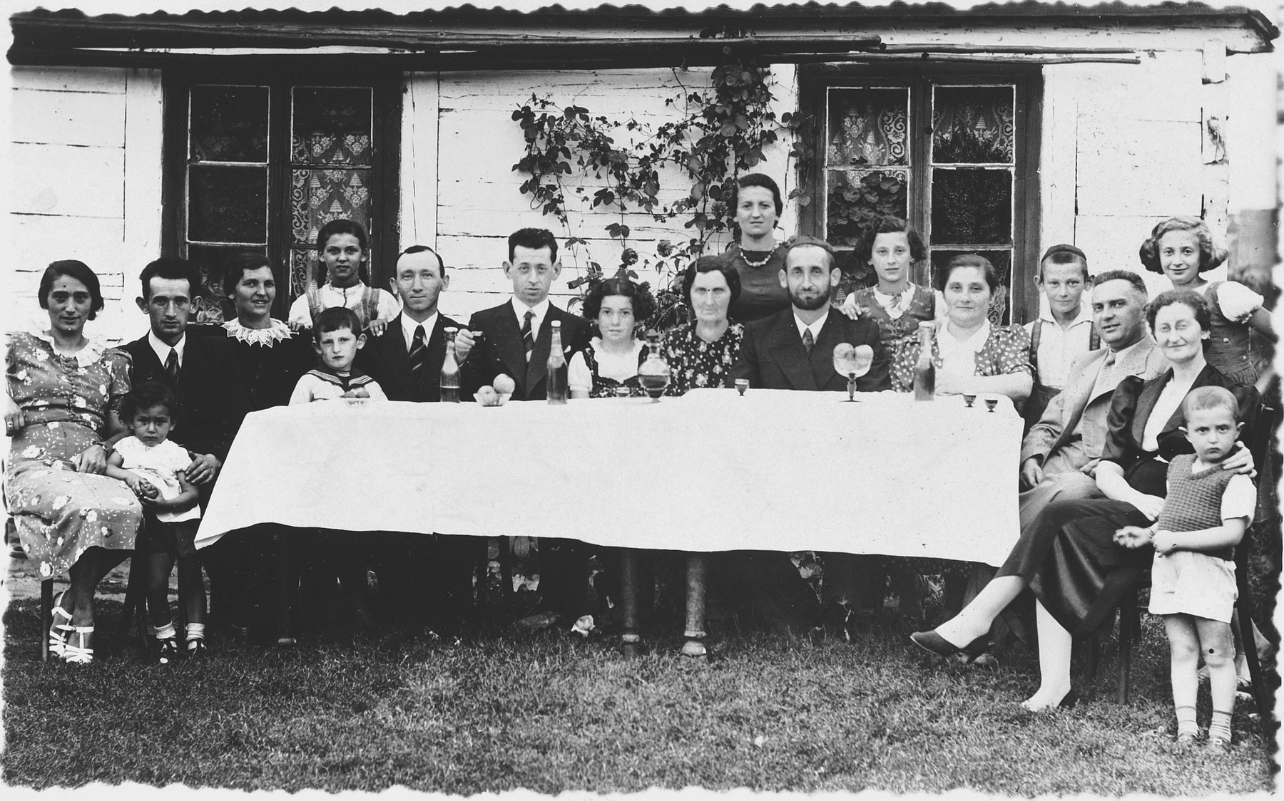 An extended Jewish family gathers around an outdoor table in prewar Zelow.