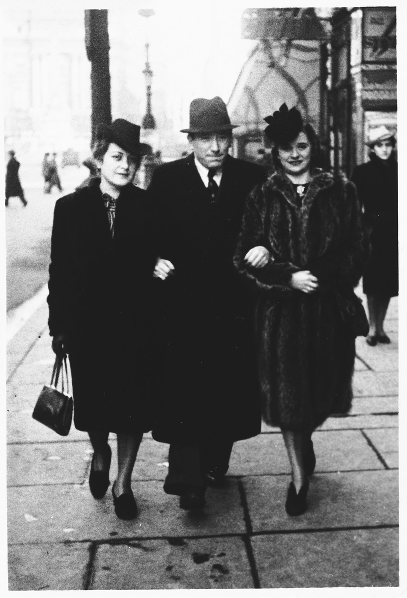 A Jewish couple strolls with a friend along a street in German-occupied Brussels.  Pictured on the left are Lea and Mendel Abramowicz.