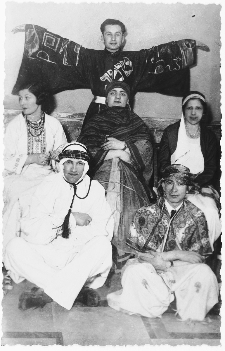A group of Jewish teenagers pose wearing costumes [possibly for a Hannukah party].  Among those pictured is Shura Mesherowsky (middle row, on the left).