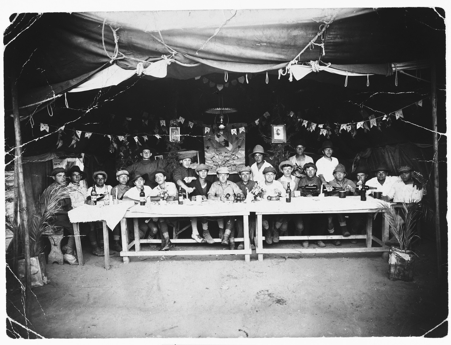 Group portrait of Jewish pioneers in a tent decorated with Zionist emblems in Palestine.  Among those pictured is Mendel Abramowicz.