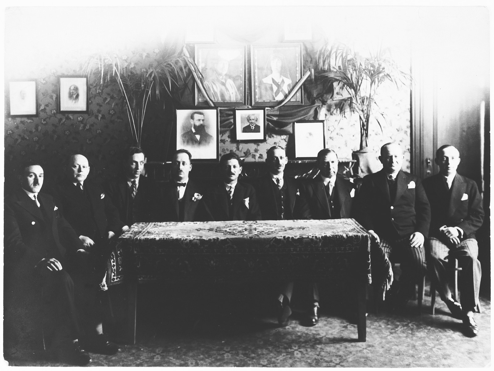 Group portrait of members of the ftraternal organizatgion of Jews from Lodz  in Antwerp, Belgium.  Among thos pictured is Emmanuel Rubinstein, on far left.  Hanging on the wall are portraits of the King and Queen, Theodore Herzl and Albert Einstein.