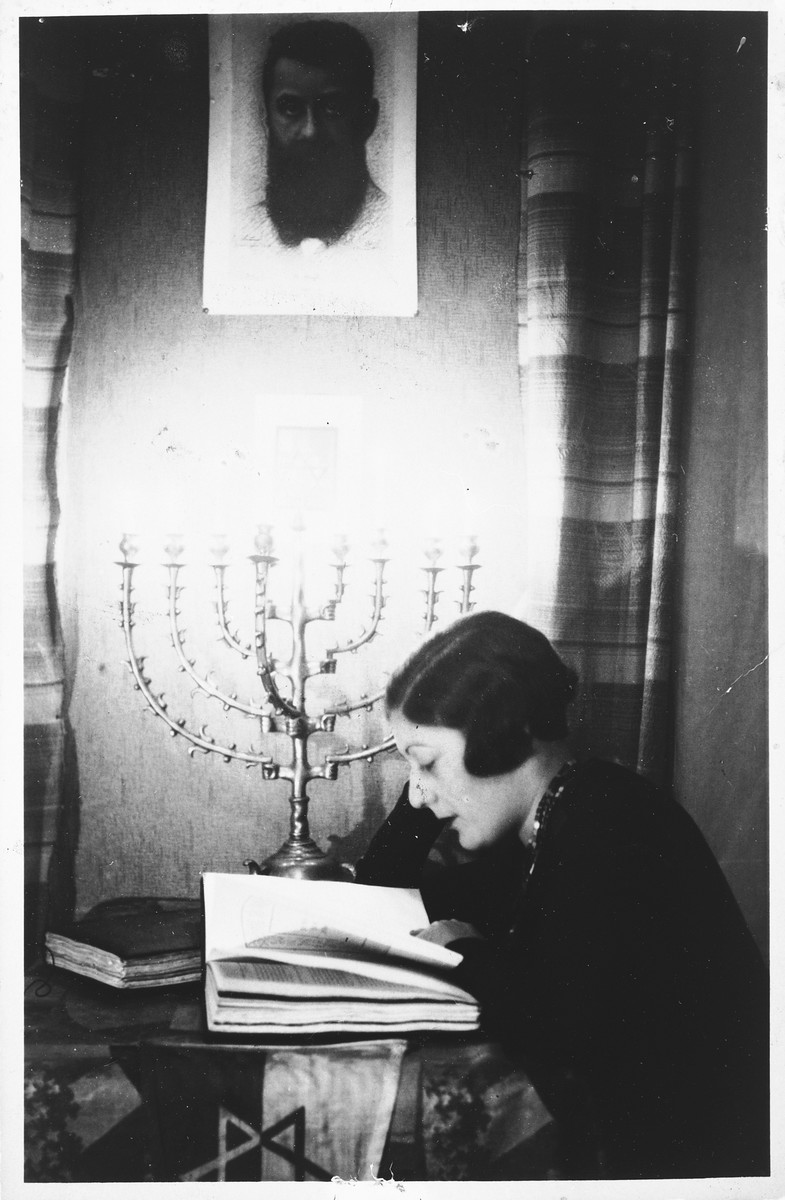 A young Jewish woman sits reading a book under a hanging portrait of Theodor Herzl.  The table is decorated with a Jewish flag and a Hanukkah menorah.    Pictured is Shura Mesherowsky.