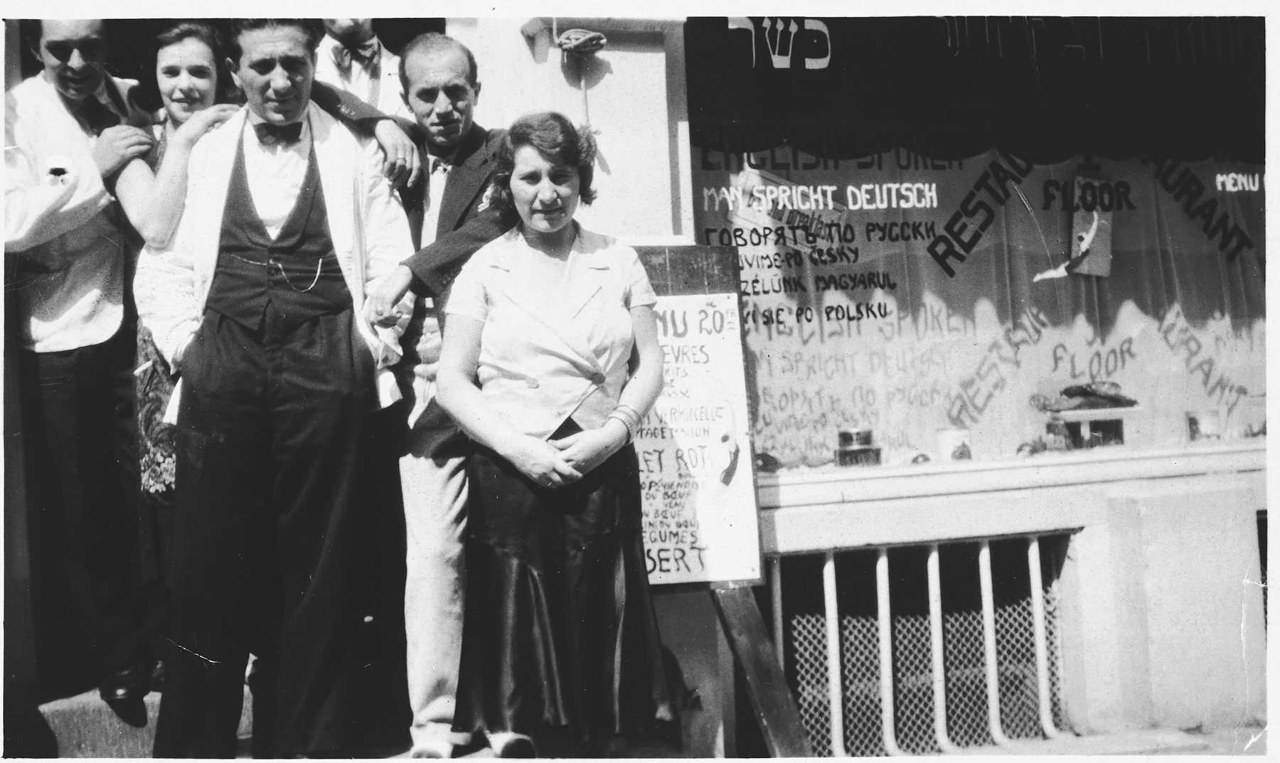 A Jewish family poses in front of their kosher restaurant in Ostend, Belgium.   Pictured in front are the three siblings, Mendel, Henri and Golda Abramowicz.  Henry was later deported to Auschwitz where he perished.