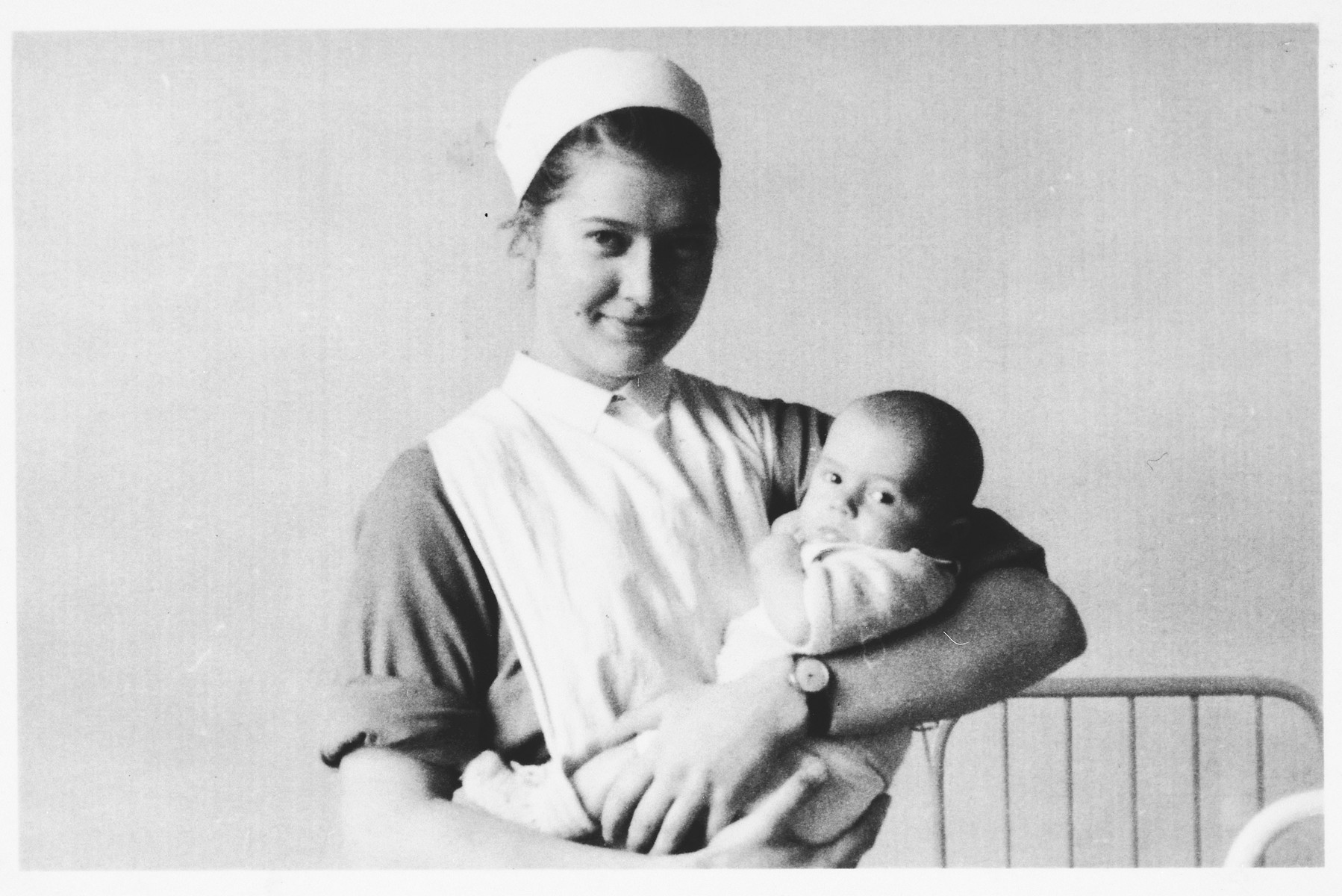 A nurse cradles a Jewish infant who is being sheltered at the Clinique Edith Cavell in Brussels, Belgium.  The infant is Georges Abramowicz.