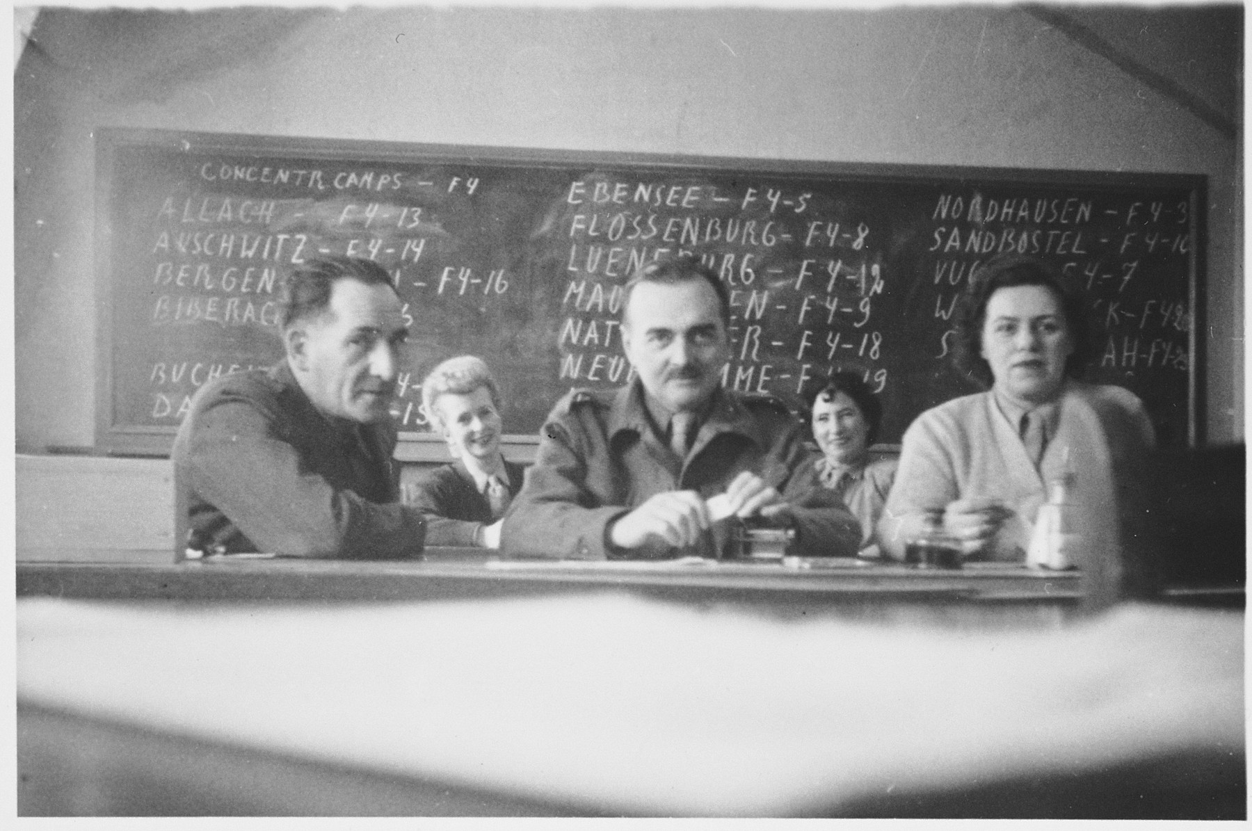 Staff of the UNRRA tracing service sit in front of a blackboard listing the file codes of different concentration camps.