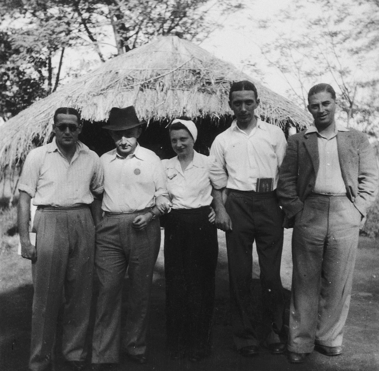 Group portrait of German-Jewish refugees in front of a thatched roof hut in Kenya.  Pictured from left to right are: Mr. Levar, Mr. Kuslinsku, Ruth Weyl, Heinrich Weyl and Mr. Kuhn.