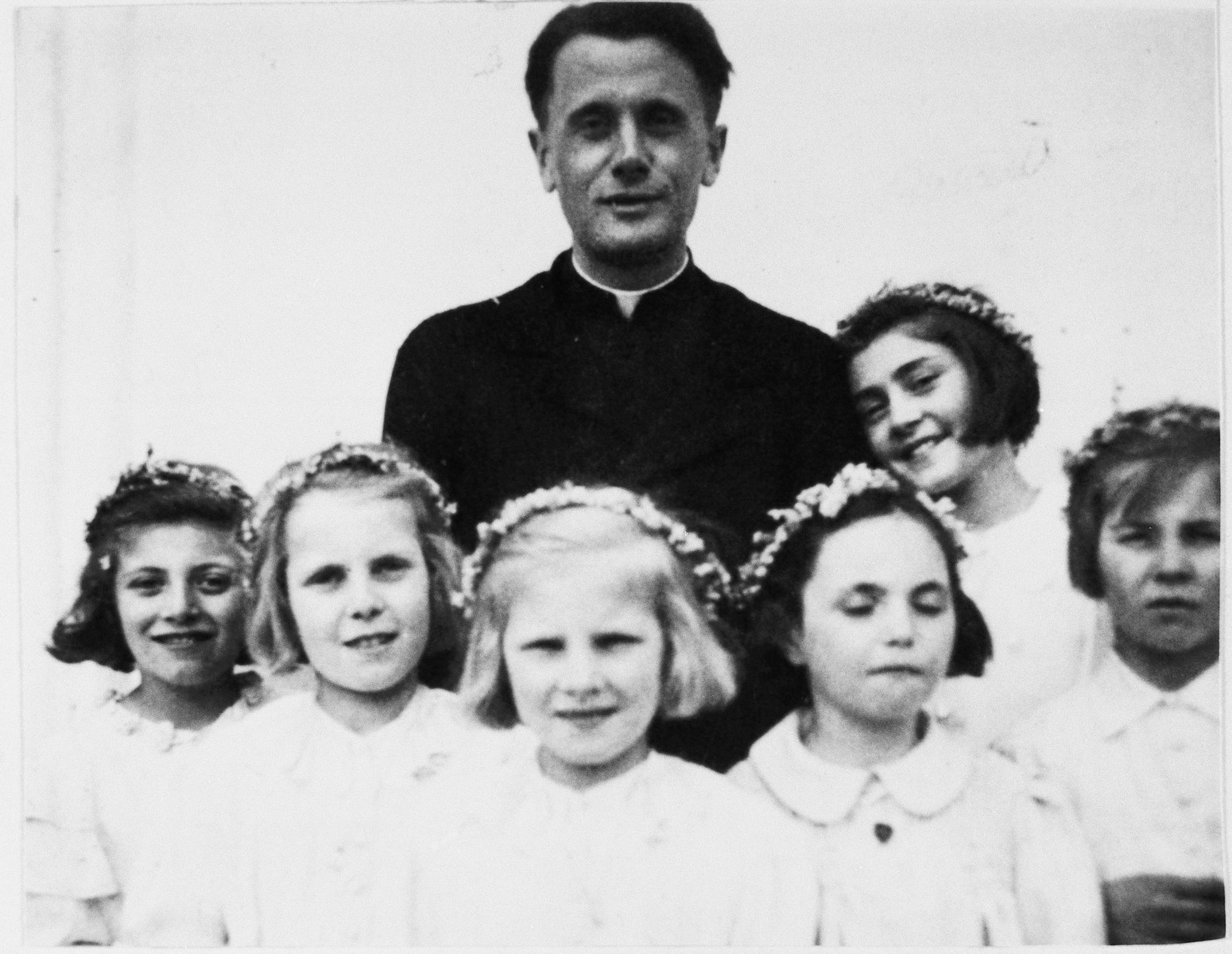 A priest poses with six young girls on the occasion of their first communion.  Standing from the left are Halina Wroncberg, and Basia and Ala Chormanskie.