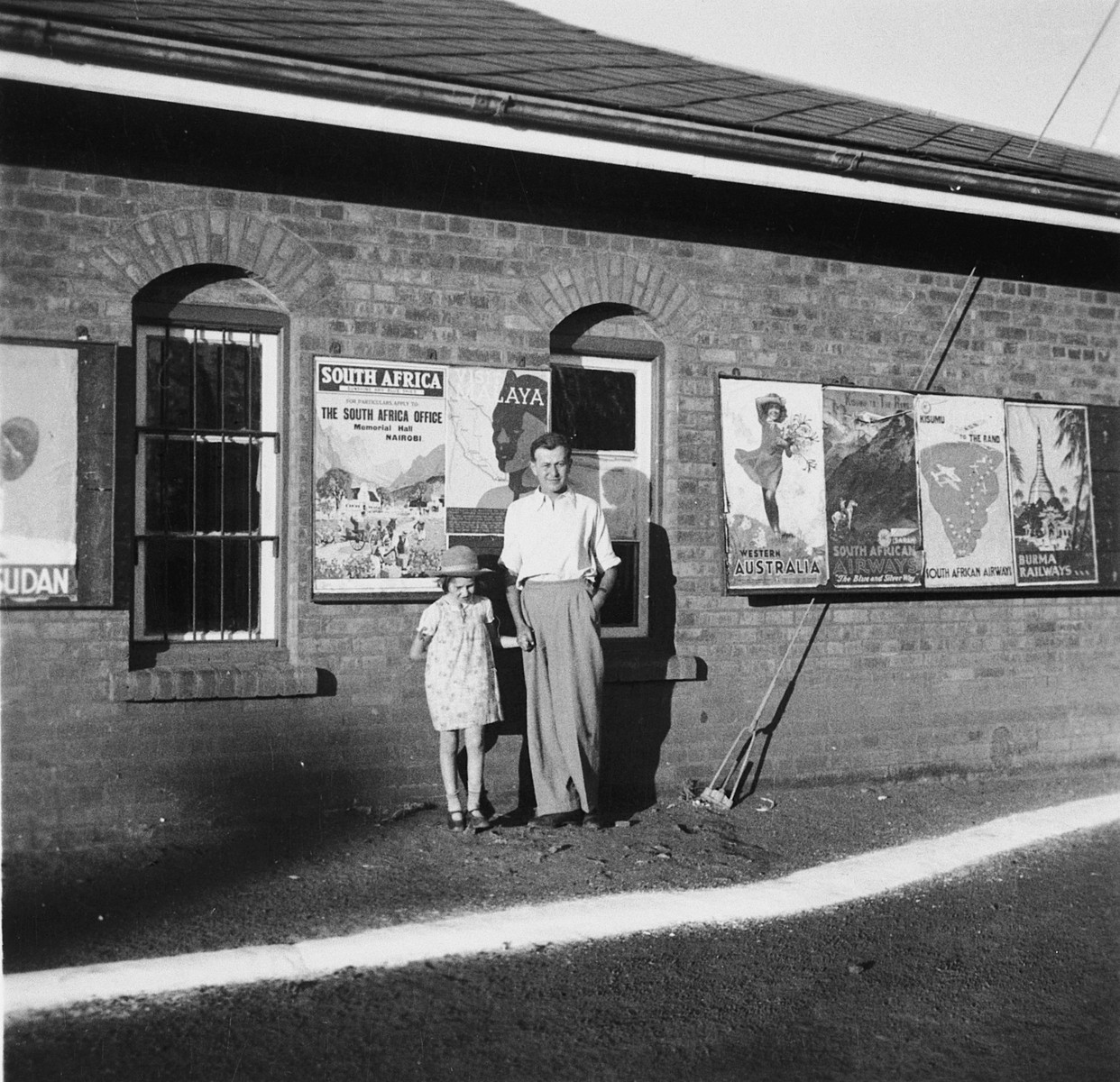 A Jewish refugee father poses with his daughter in front of a building covered with travel posters in Kenya.  The daughter is Stefanie Zweig.