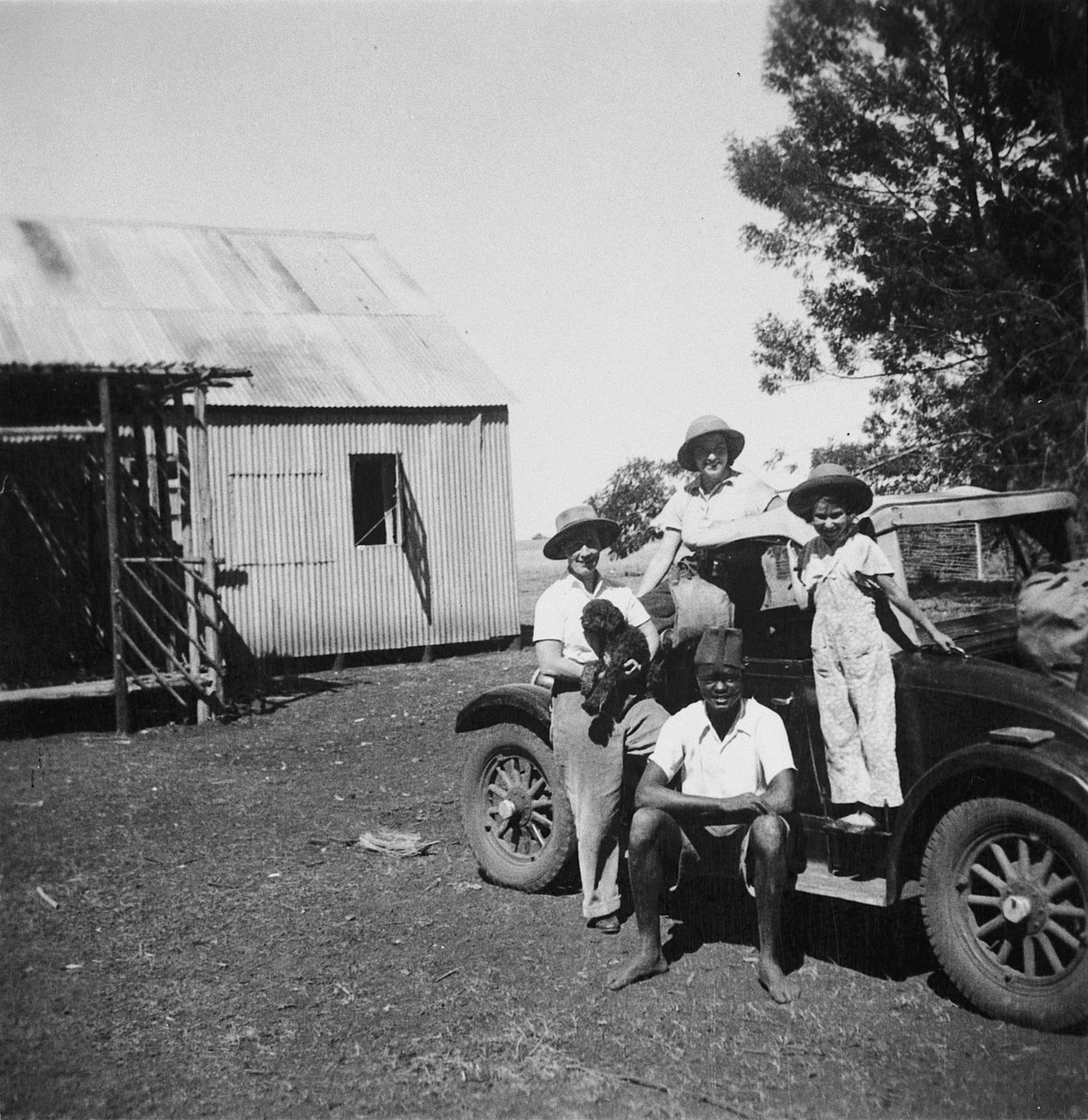 Members of a Jewish refugee family pose with an African assistant in front of their car on their farm in Kenya.  Pictured are members of the Zweig family.  Stefanie Zweig is on the right.
