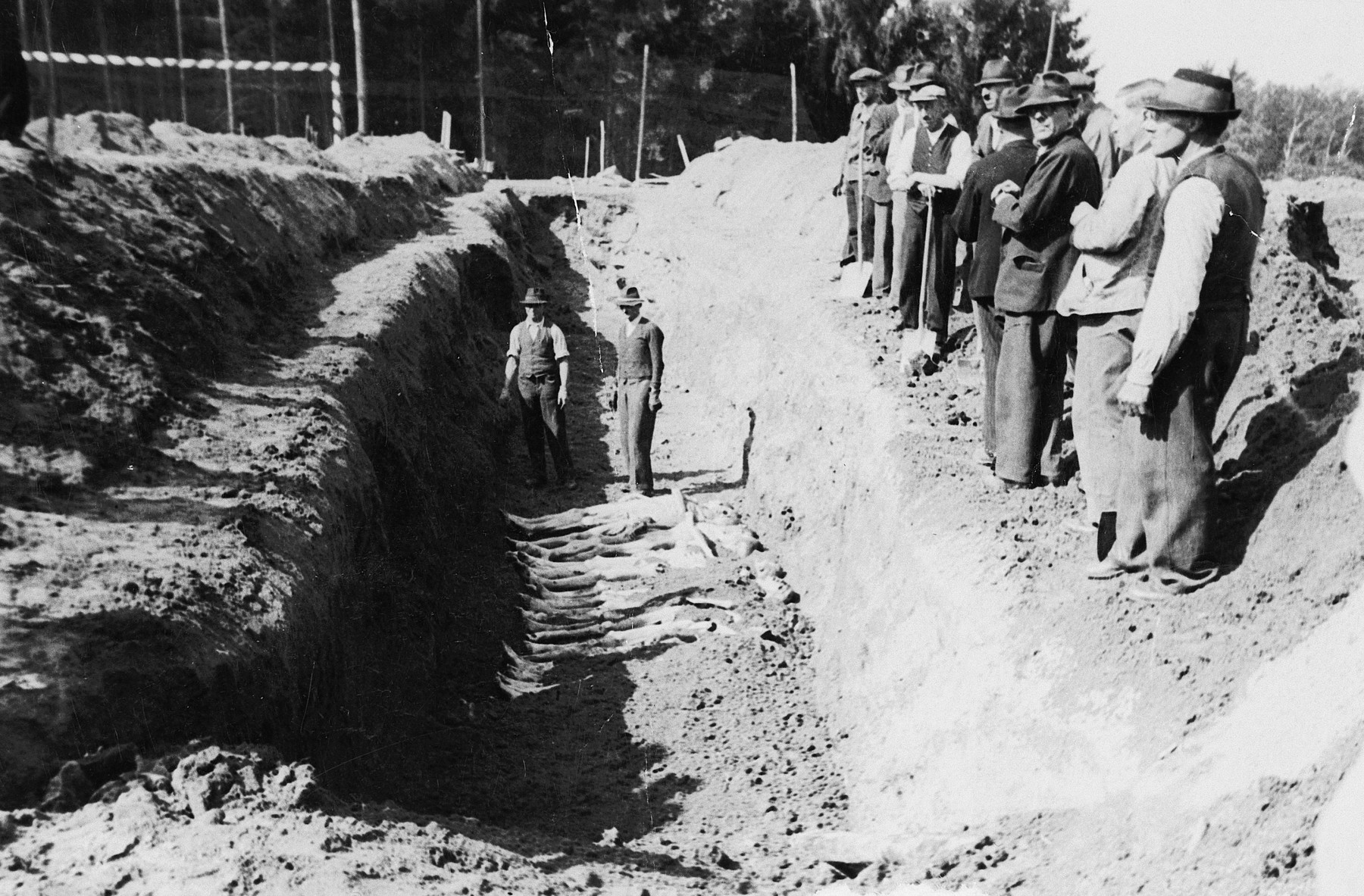 Austrian civilians are forced to bury corpses in a mass grave in the Mauthausen concentration camp.